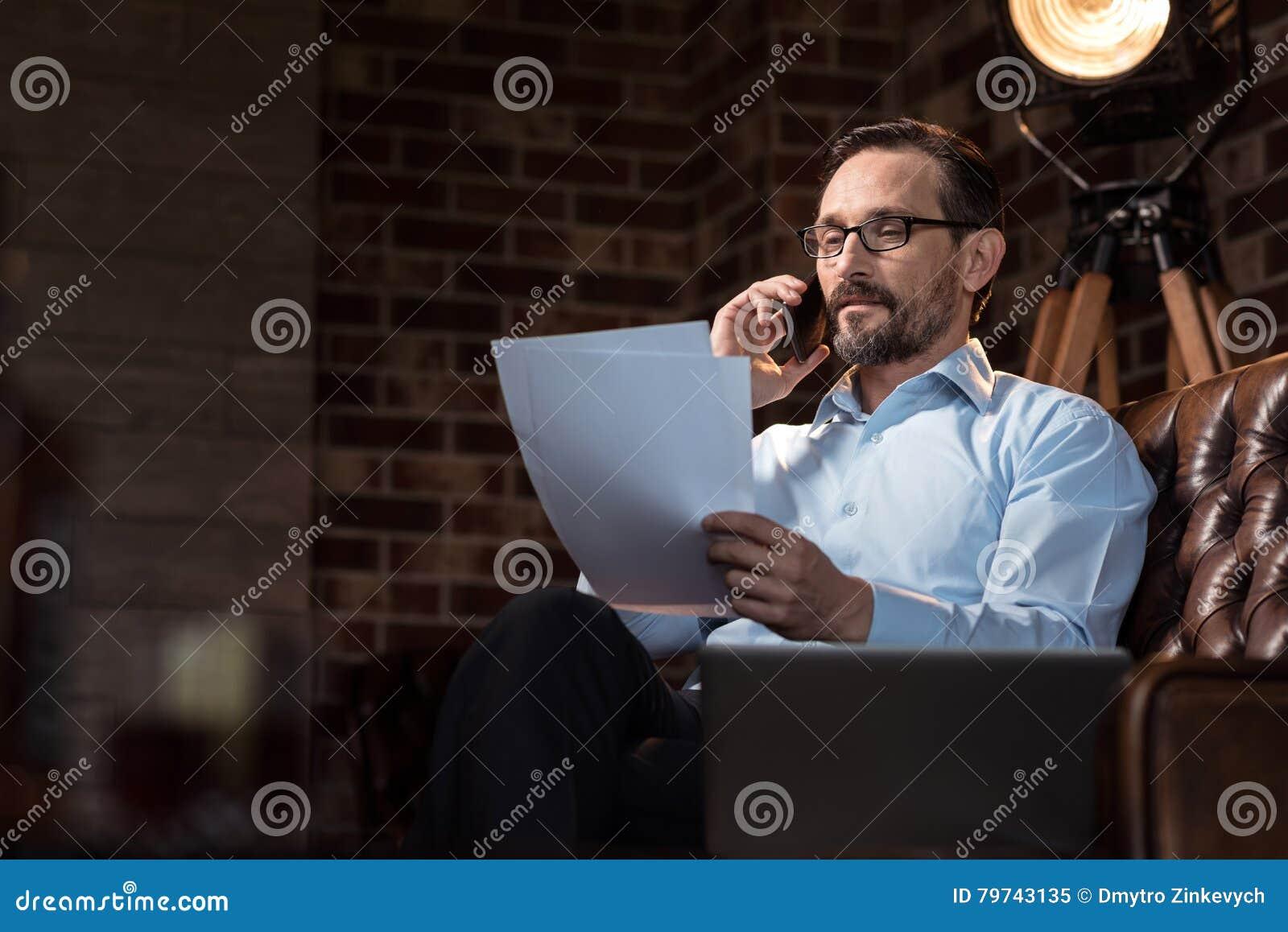 Hombre de negocios elegante alegre que pone un smartphone a su oído
