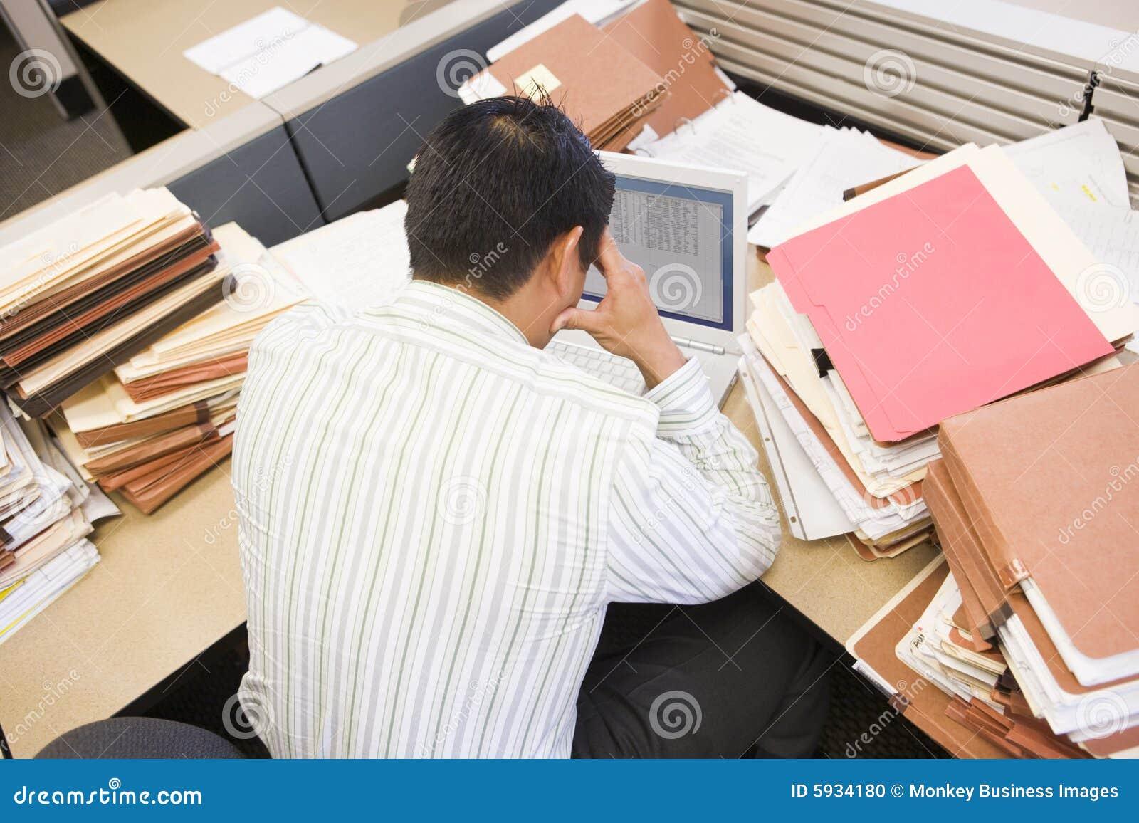 Hombre de negocios en cubículo con la computadora portátil