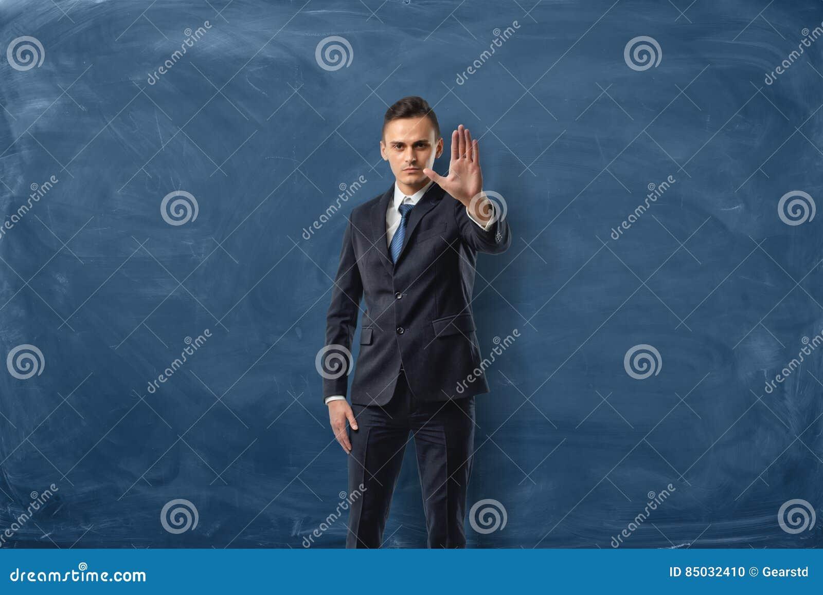 Hombre de negocios en el fondo azul de la pizarra que lleva a cabo una mano en una muestra de la parada