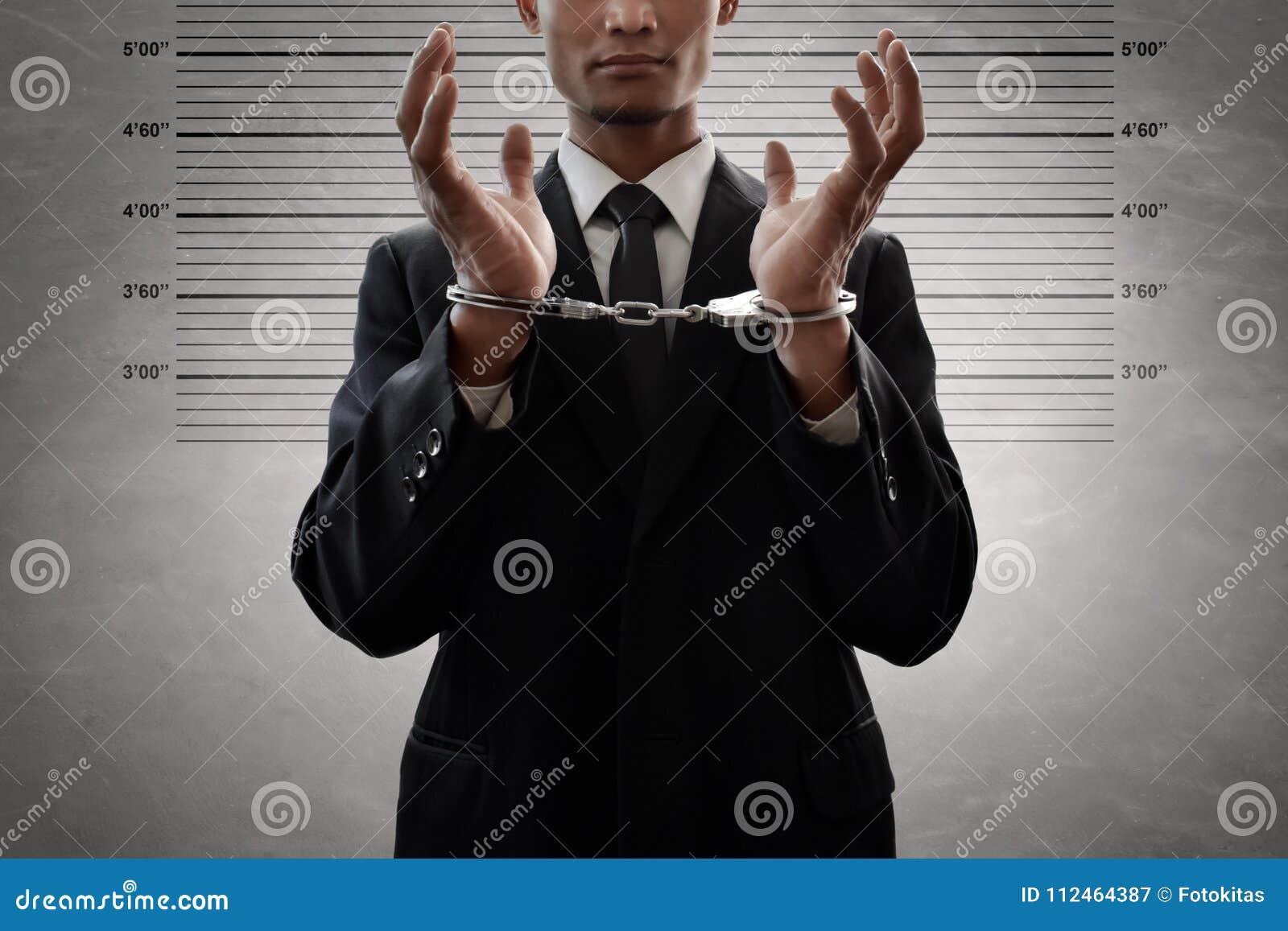 Hombre de negocios en esposas en fondo del mugshot