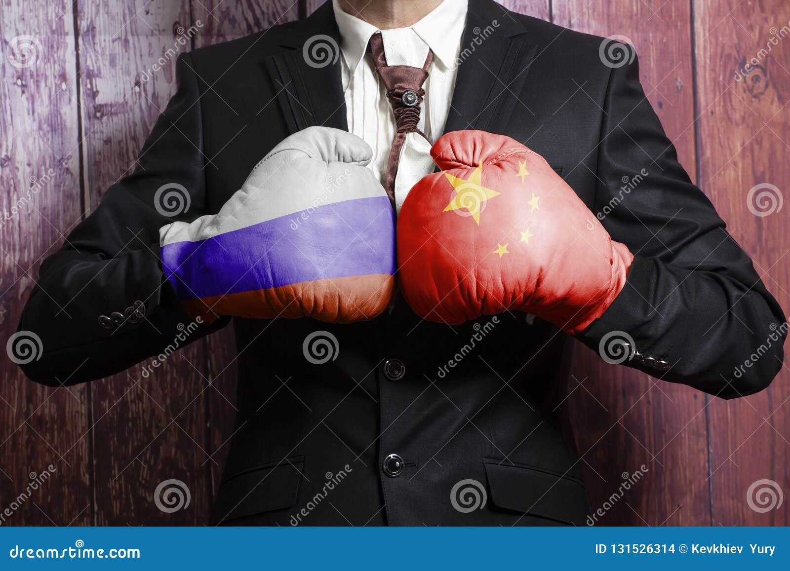 Hombre de negocios en guantes de boxeo con la bandera del ruso y de China Rusia contra el concepto de China