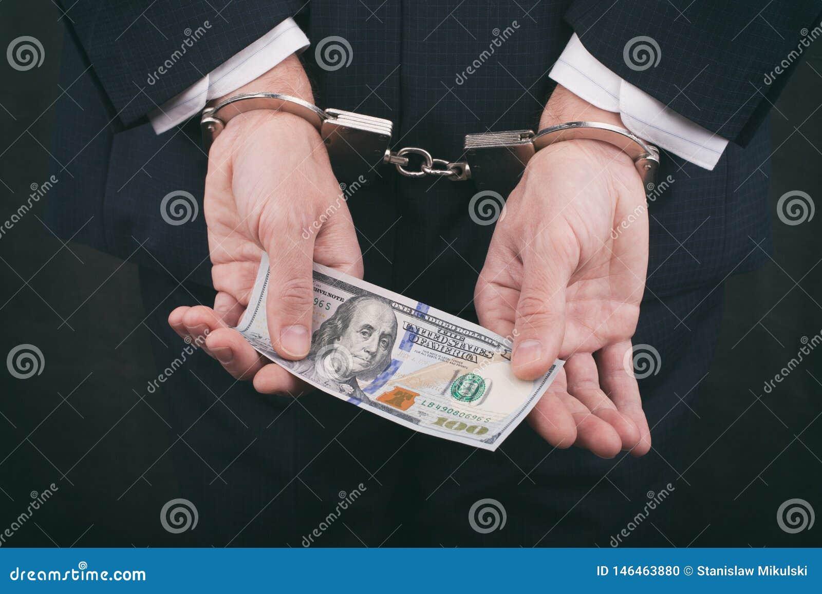 Hombre de negocios en las esposas que sostienen el soborno cientos dólares