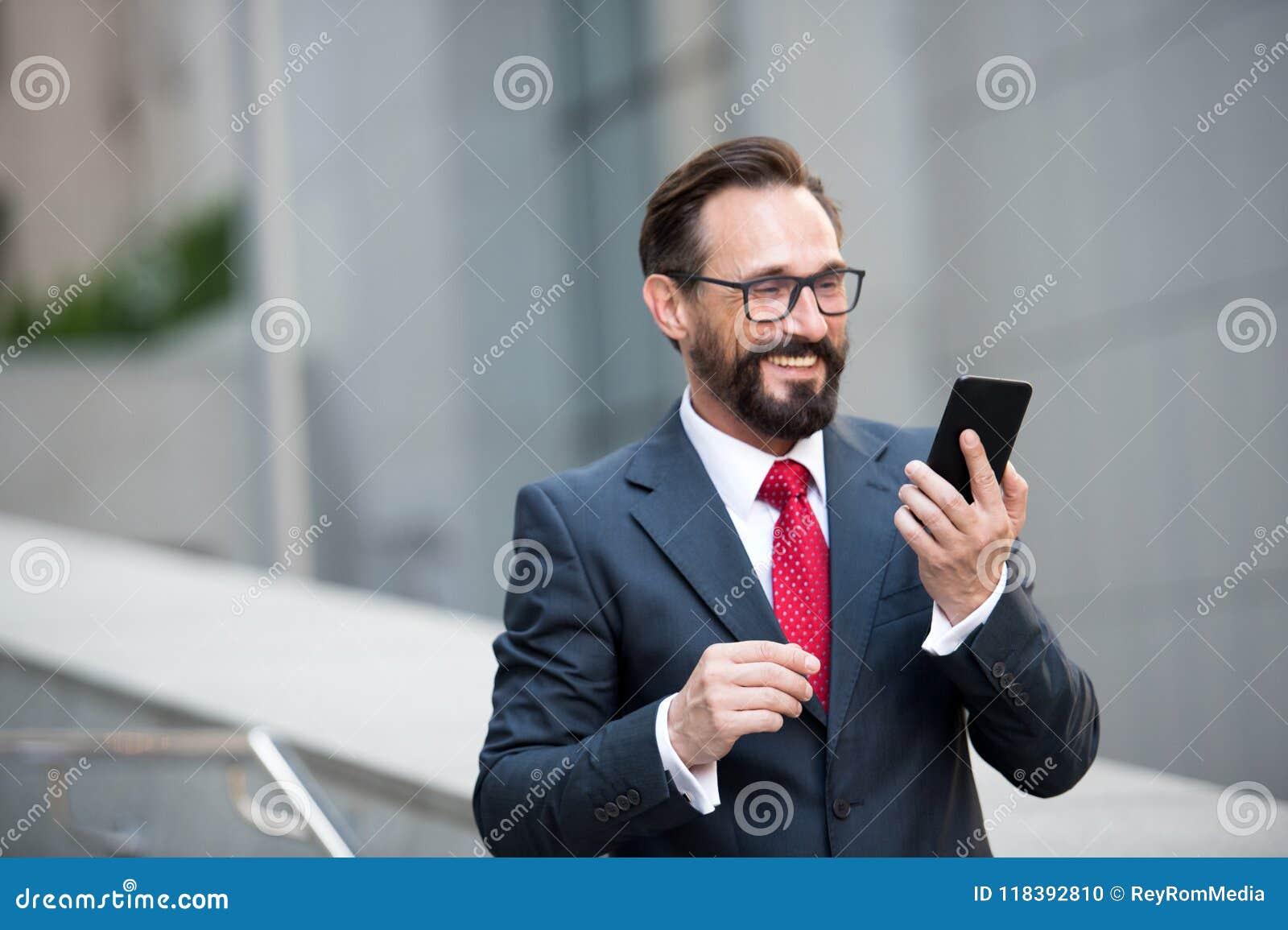 Hombre de negocios en vidrios usando el teléfono elegante en la calzada de la oficina con el fondo del edificio de la ciudad Conc
