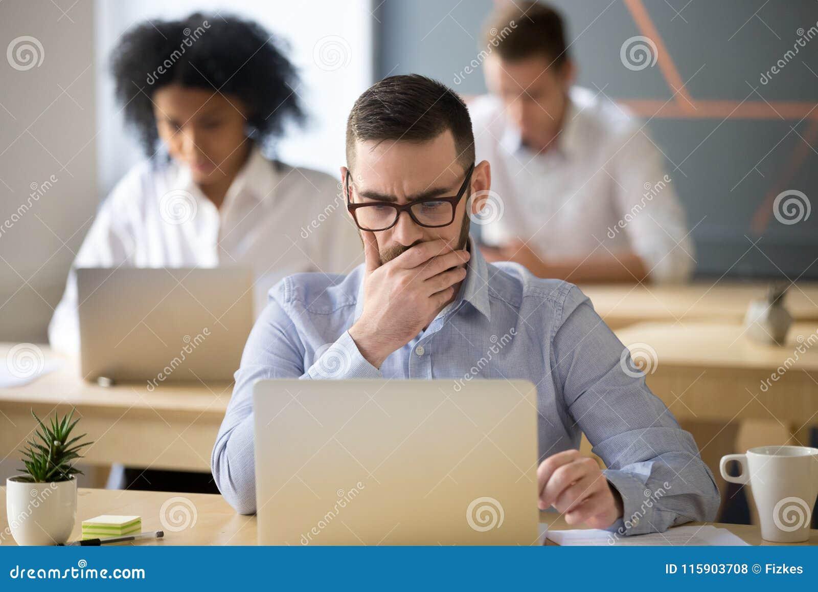 Hombre de negocios enfocado que soluciona el problema en línea que trabaja en el ordenador portátil adentro