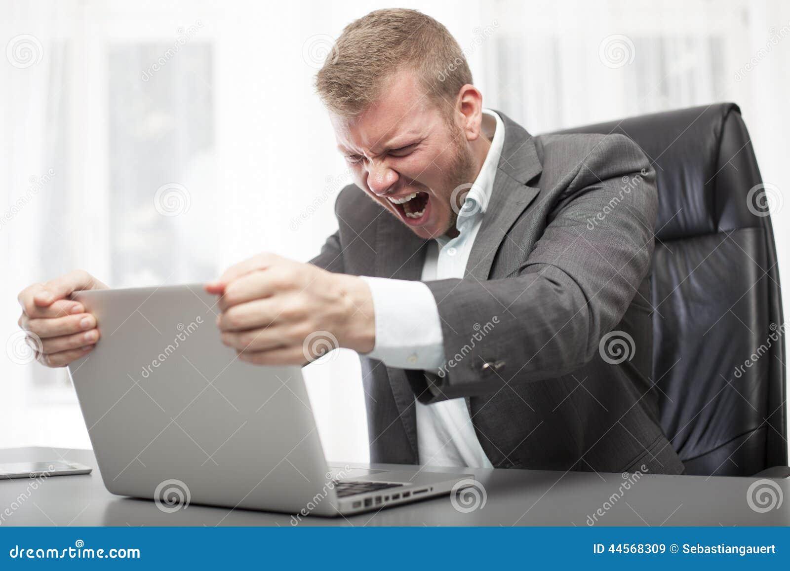 Hombre de negocios enojado que sacude su ordenador portátil