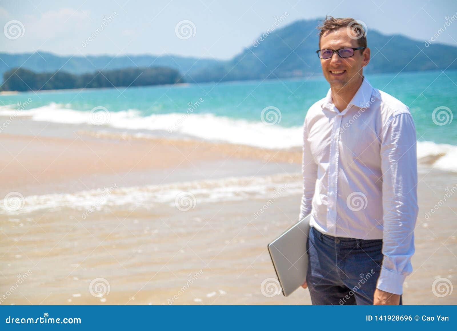 Hombre de negocios feliz en camisa con un ordenador port?til y con los vidrios que camina en la playa