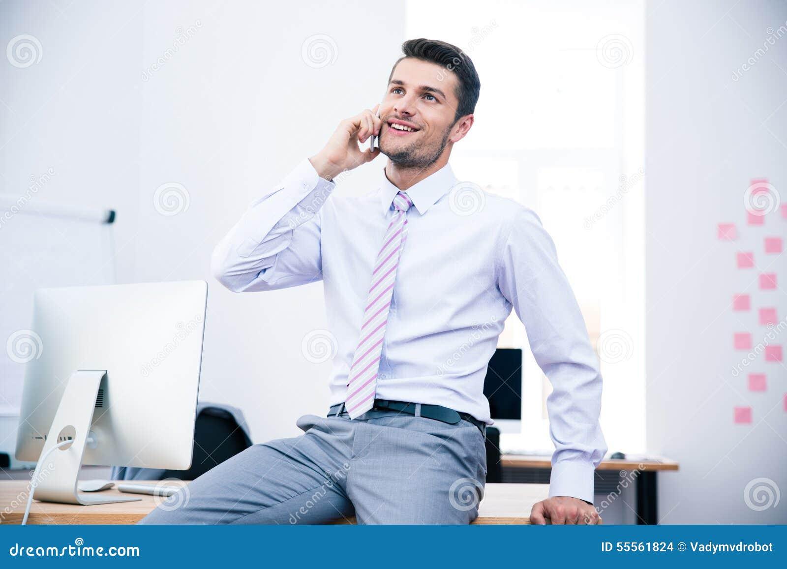 Hombre de negocios feliz que habla en el teléfono en oficina