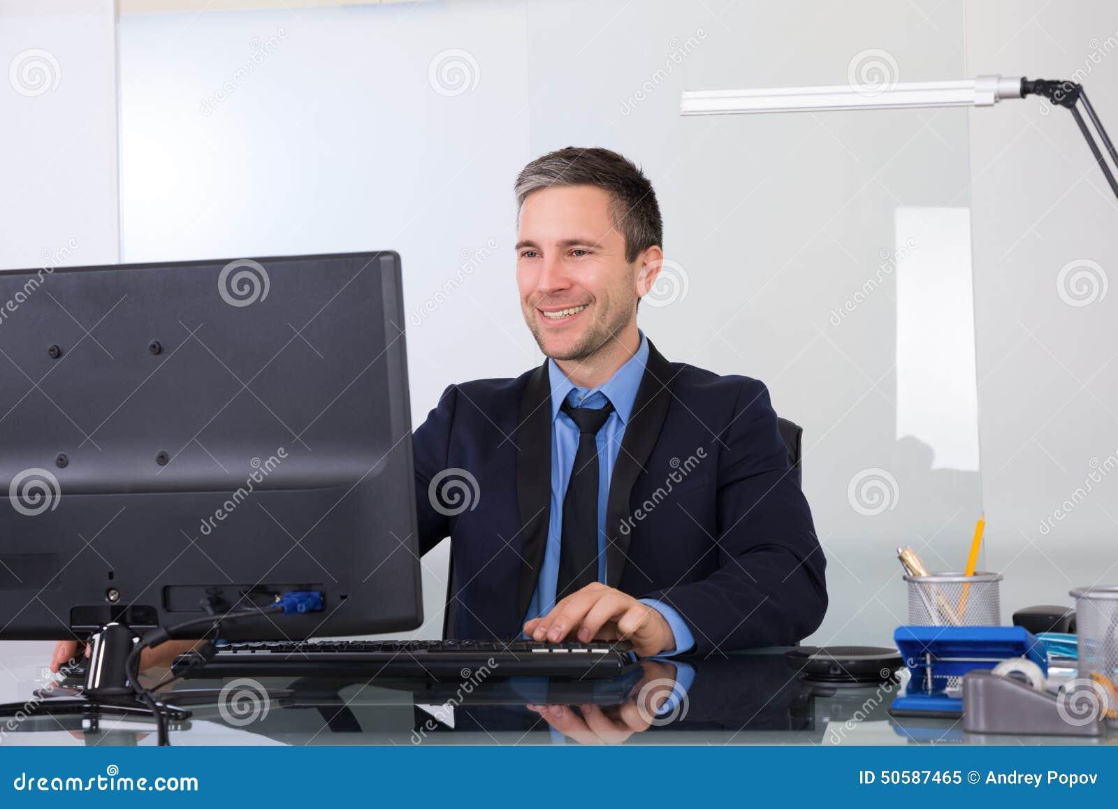 Hombre de negocios feliz usando el ordenador en su oficina