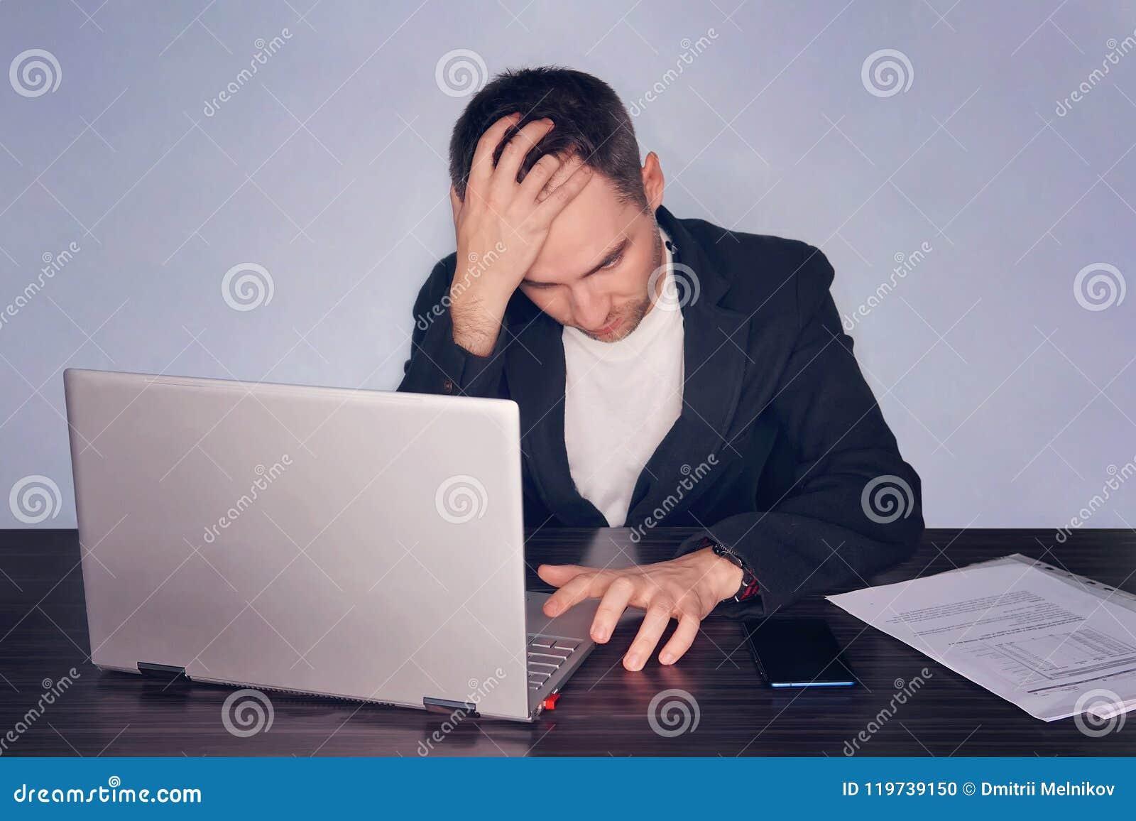 Hombre de negocios frustrado serio que sufre de jaqueca del dolor de cabeza en el lugar de trabajo Sensación cansado agotado Stre