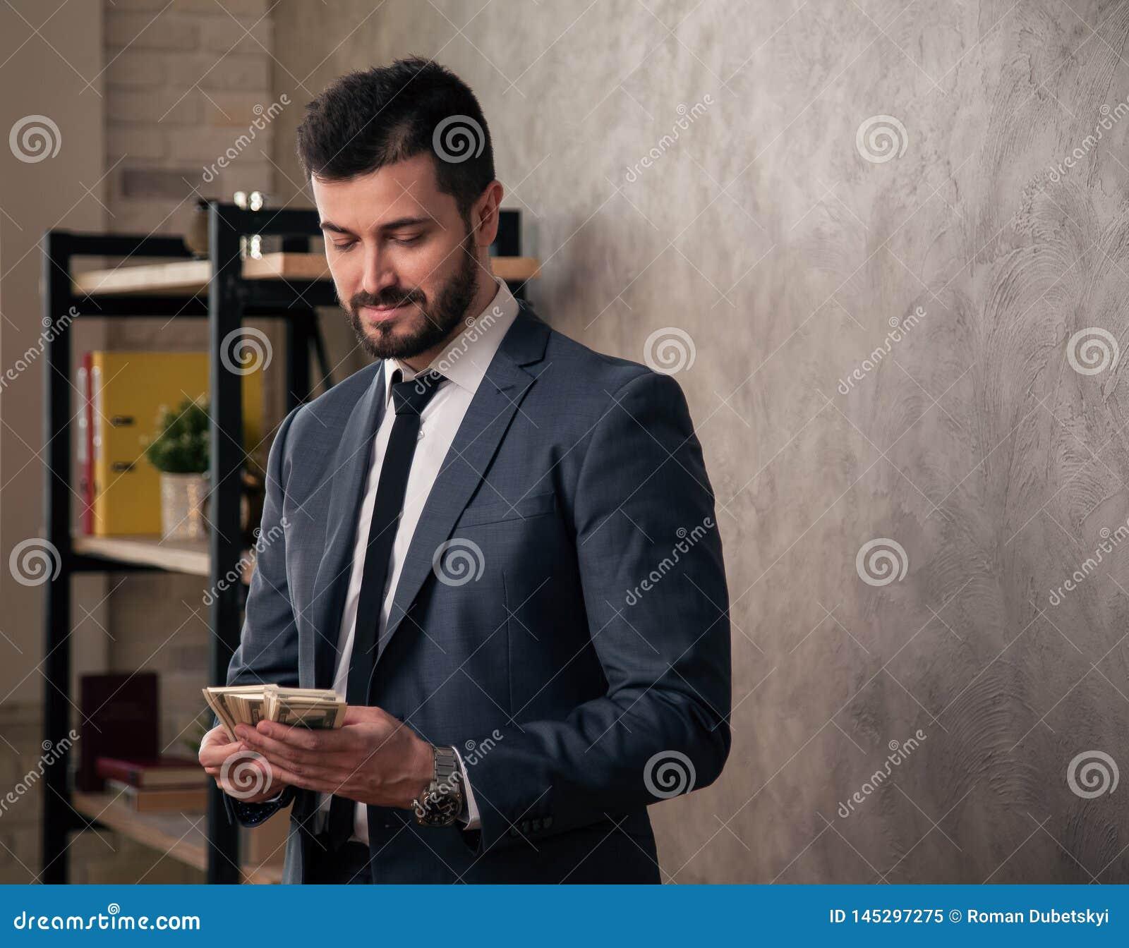 Hombre de negocios hermoso apuesto en la oficina que hace una pausa su escritorio y que cuenta el dinero traje que lleva y un laz