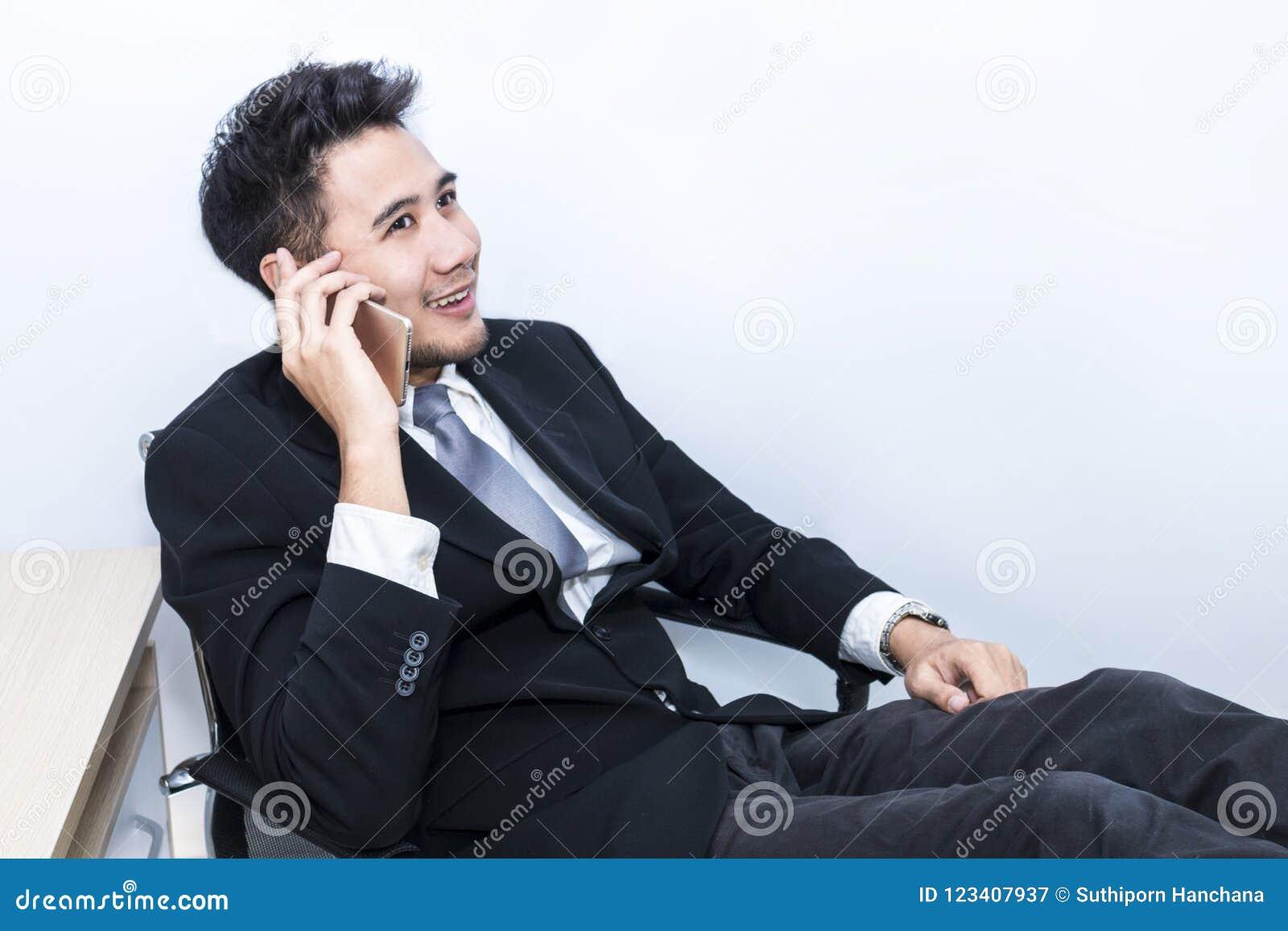 Hombre de negocios hermoso joven que sonríe y que habla con el teléfono en la oficina