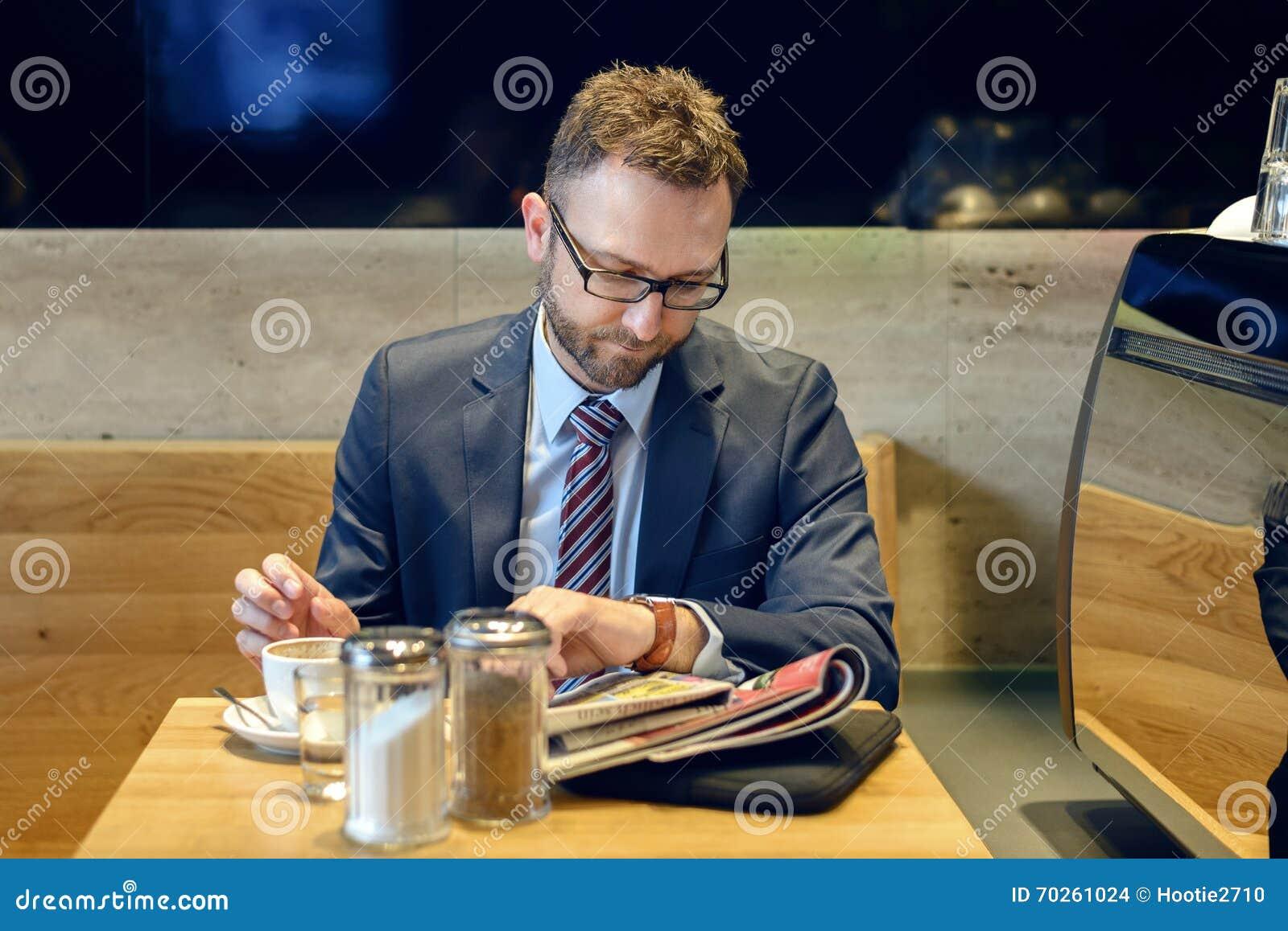 Hombre de negocios hermoso que se sienta en la tabla con la lectura del café