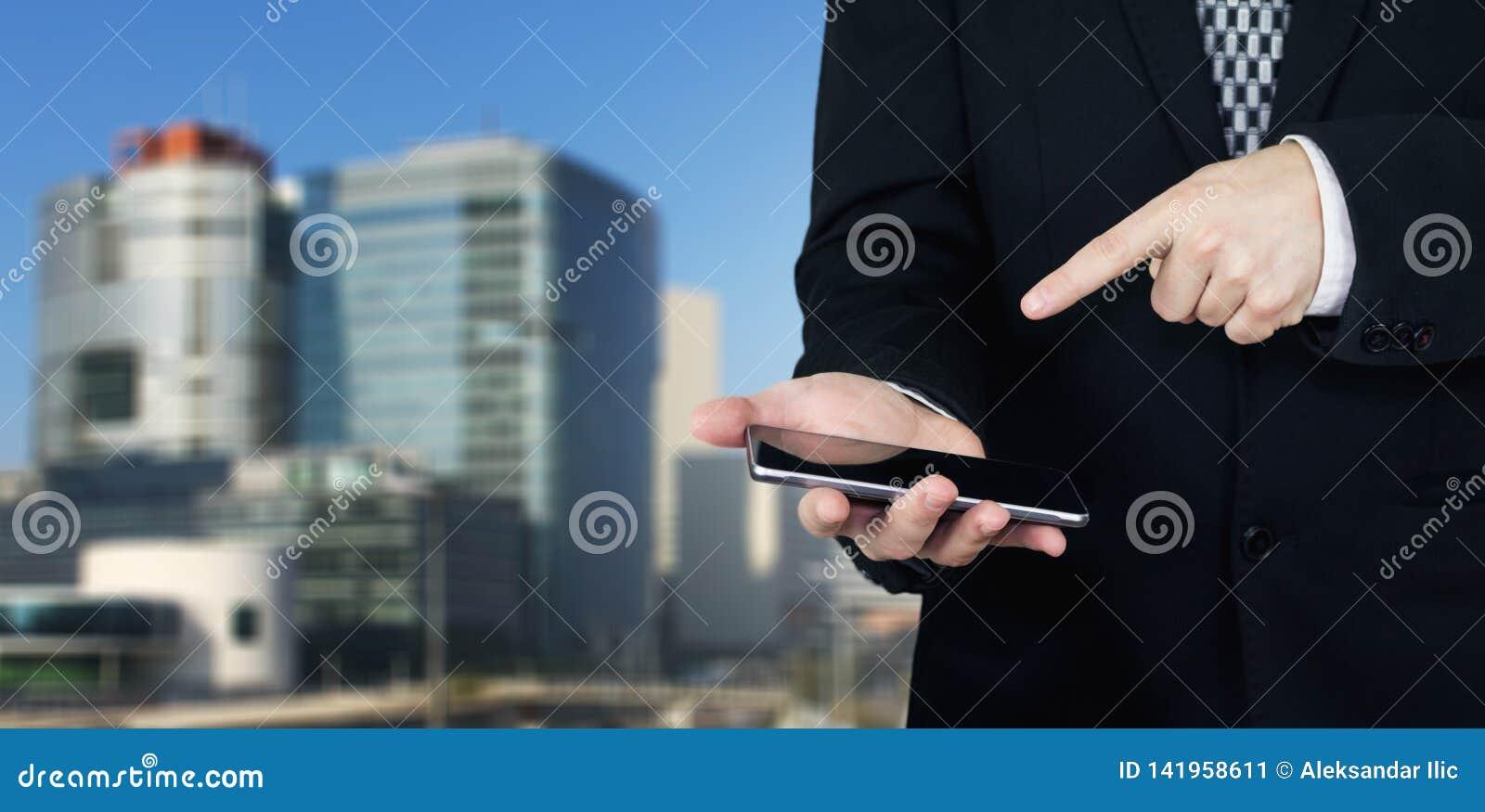 Hombre de negocios Holding Smartphone disponible y que señala el dedo índice en la pantalla de los teléfonos con la ciudad del ne