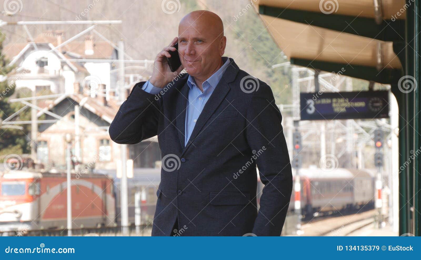 Hombre de negocios Image Smiling y el hablar con el teléfono móvil en una estación de tren