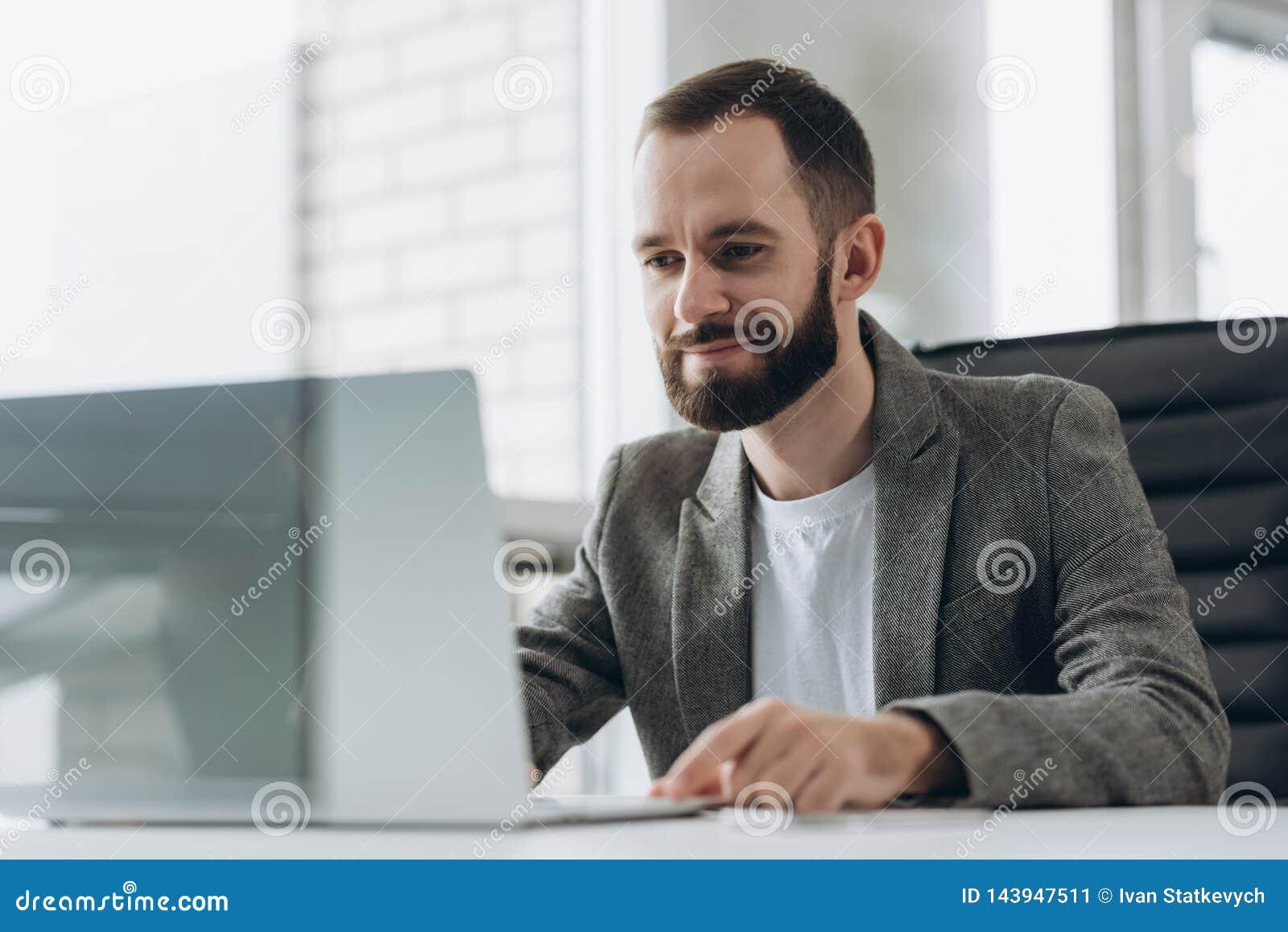 Hombre de negocios joven barbudo que trabaja en la oficina moderna Sirva la camisa blanca que lleva y las notas de la fabricaci?n