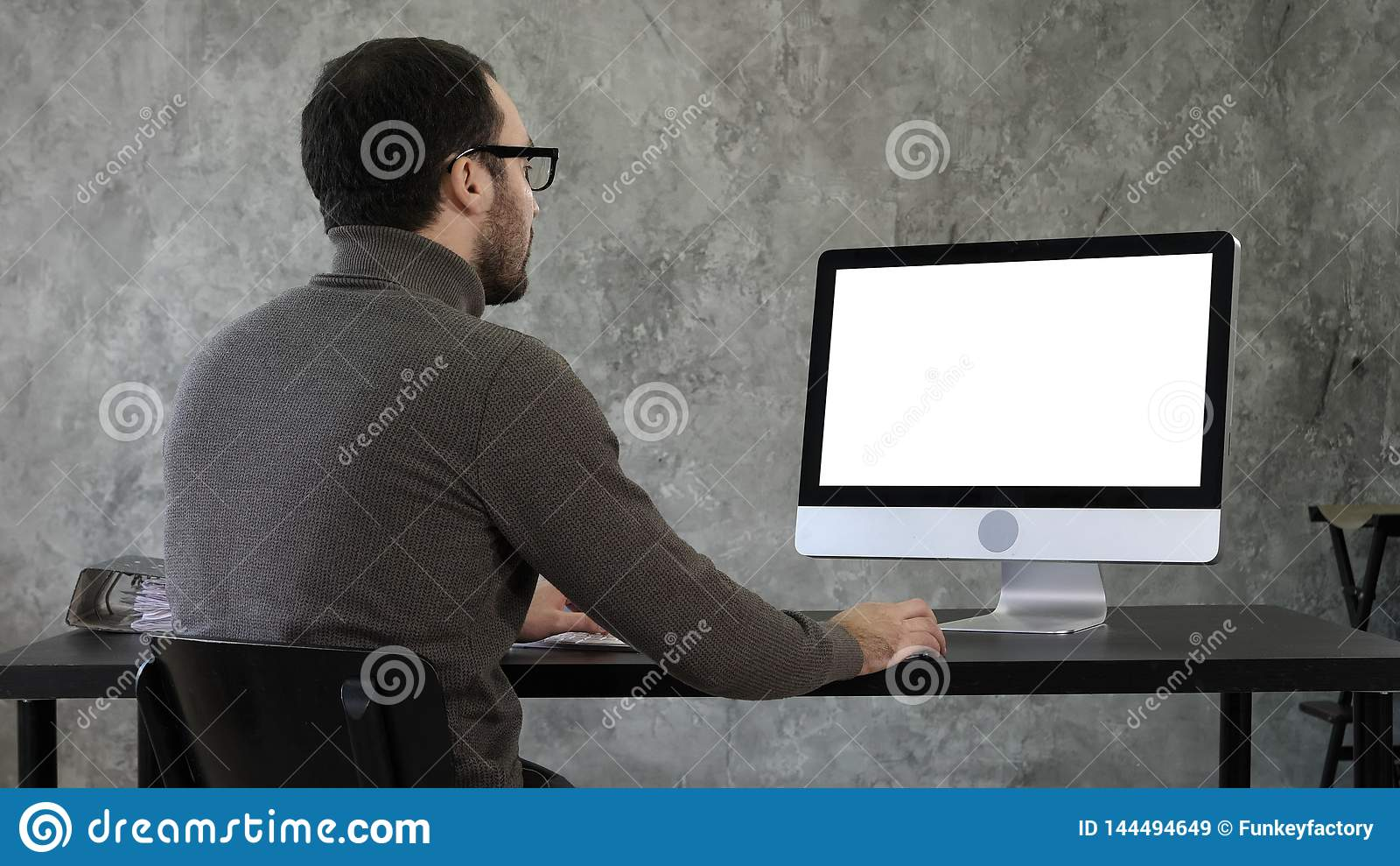 Hombre de negocios joven barbudo woking en el ordenador Visualización blanca