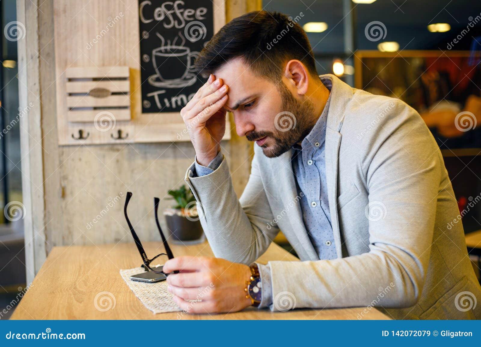 Hombre de negocios joven cansado en una rotura en cafetería