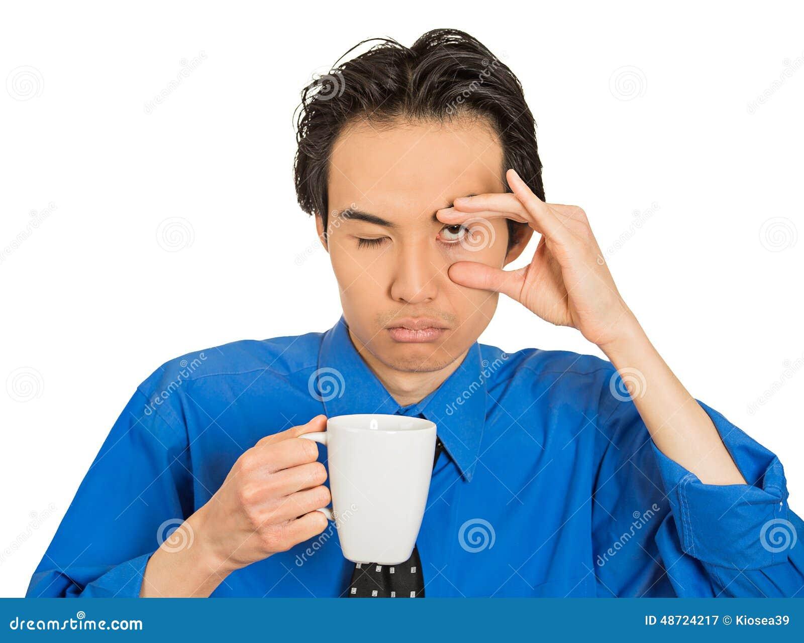 Hombre de negocios joven dormido que cae cansado que sostiene la taza de café