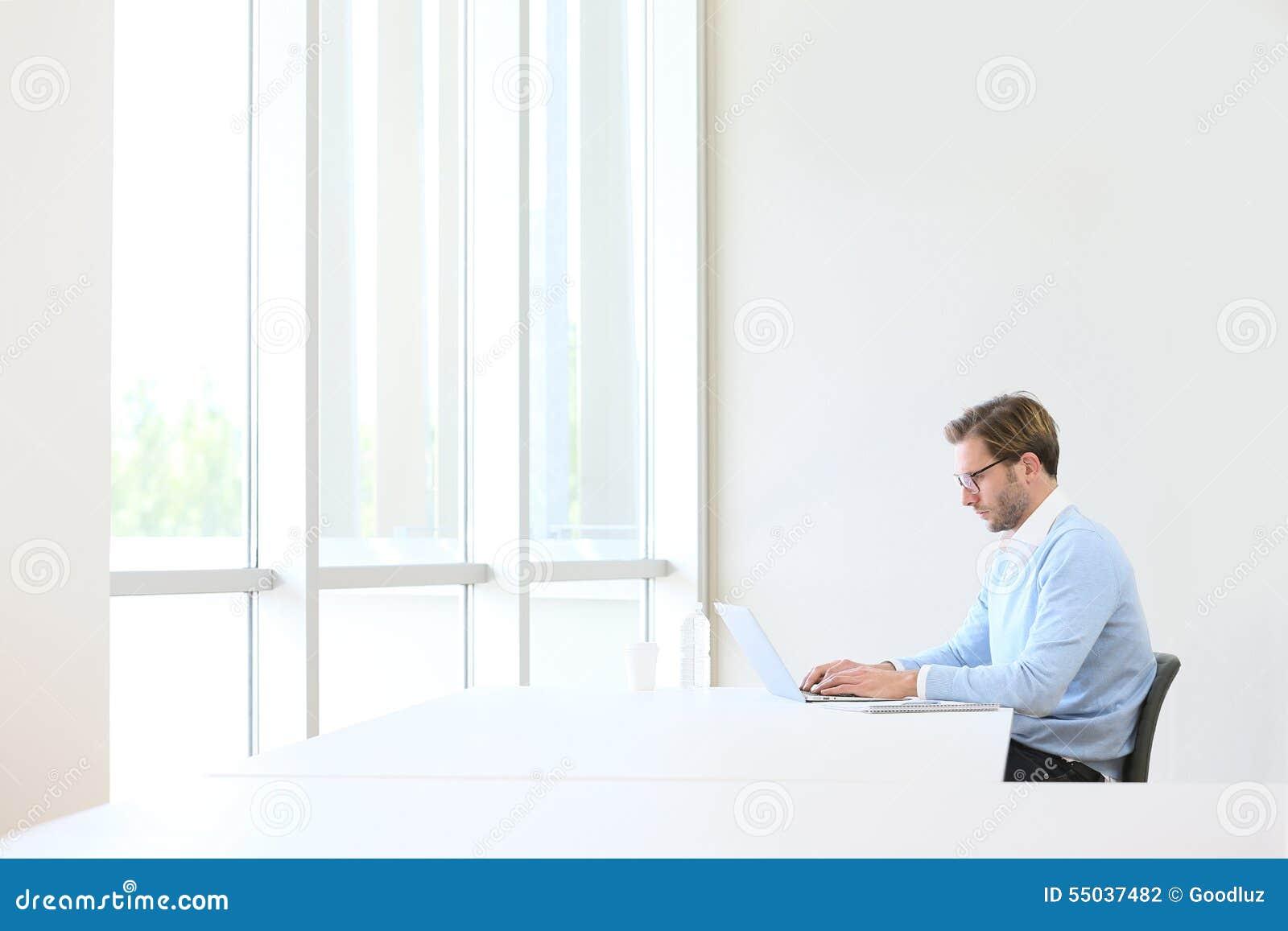 Hombre de negocios joven en el ordenador portátil aislado