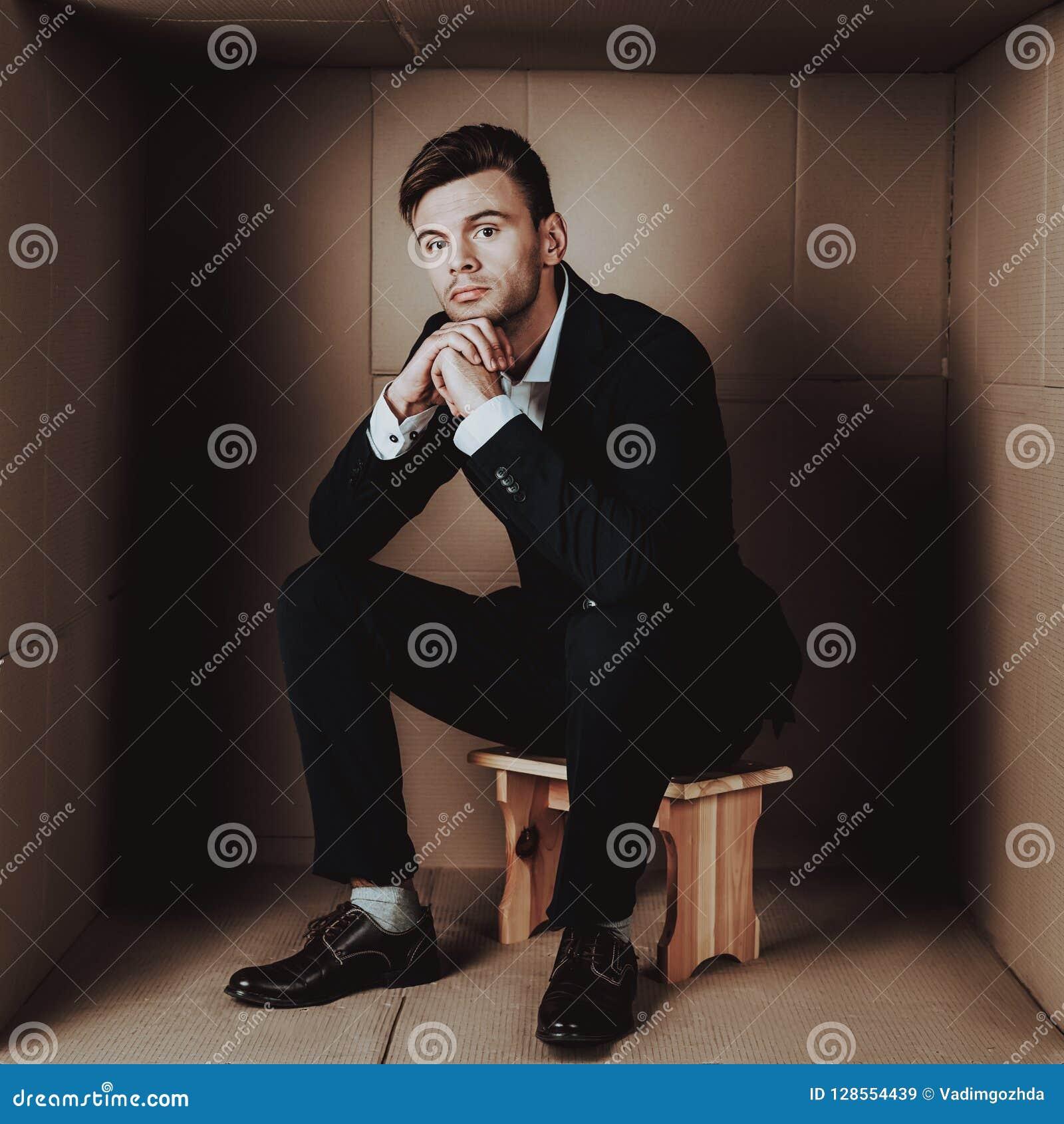 Hombre de negocios joven en traje negro en caja de cartón