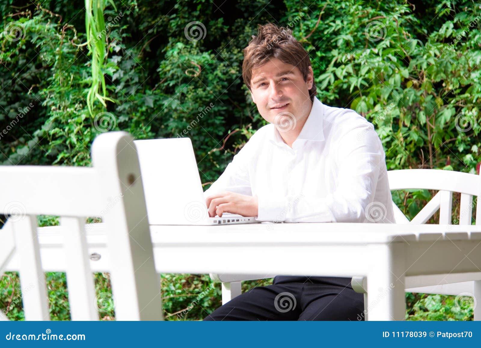 Hombre de negocios joven feliz al aire libre con la computadora portátil