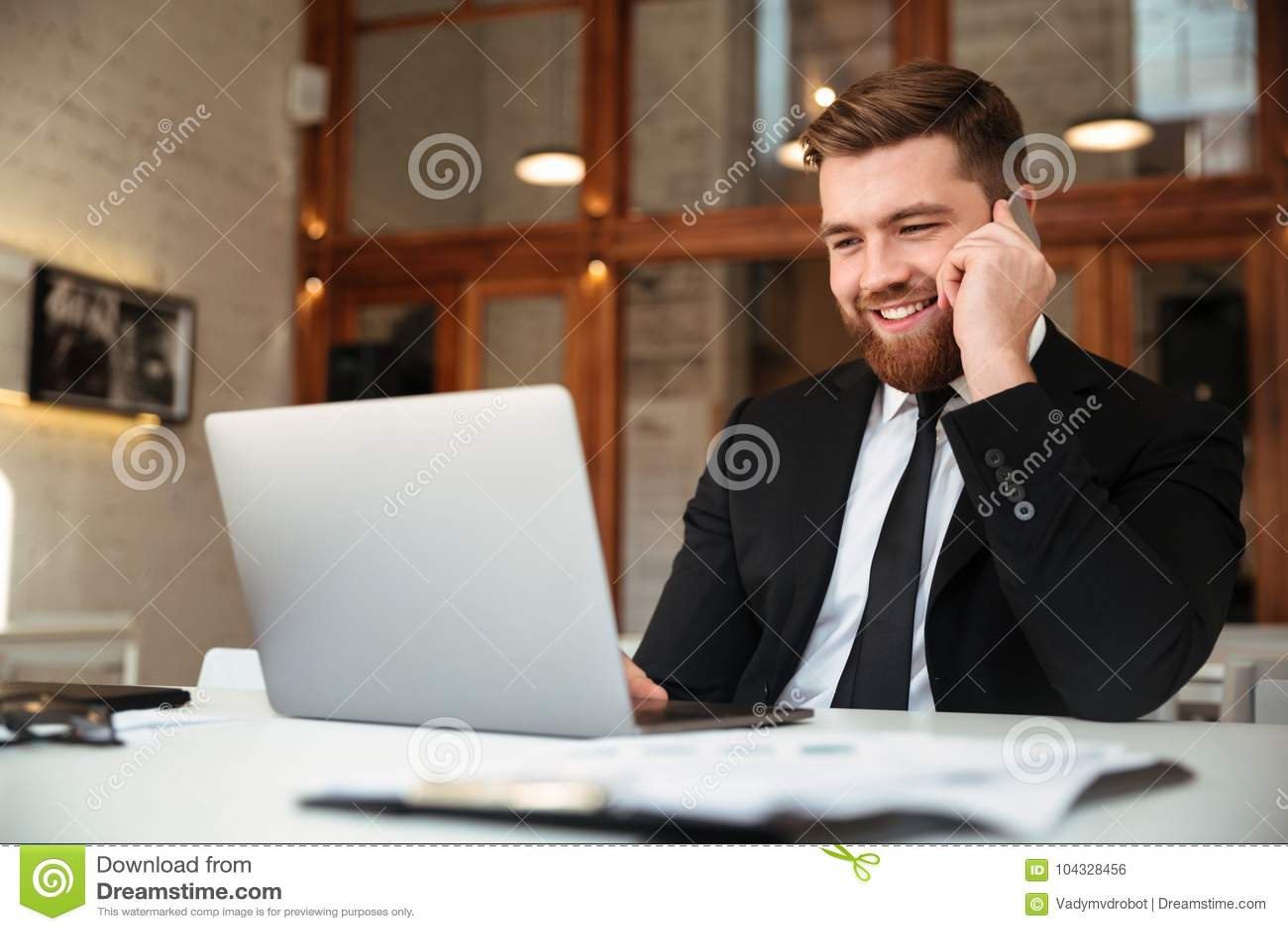 Hombre de negocios joven feliz en traje negro que habla en el teléfono móvil, l