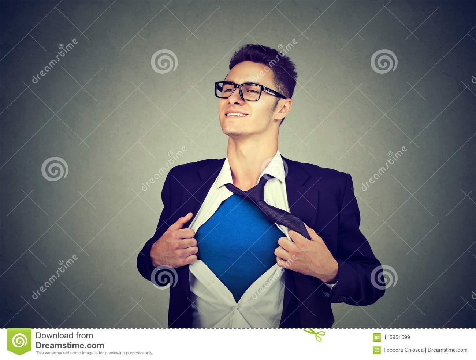 Hombre de negocios joven que actúa como un superhéroe que rasga su camisa apagado