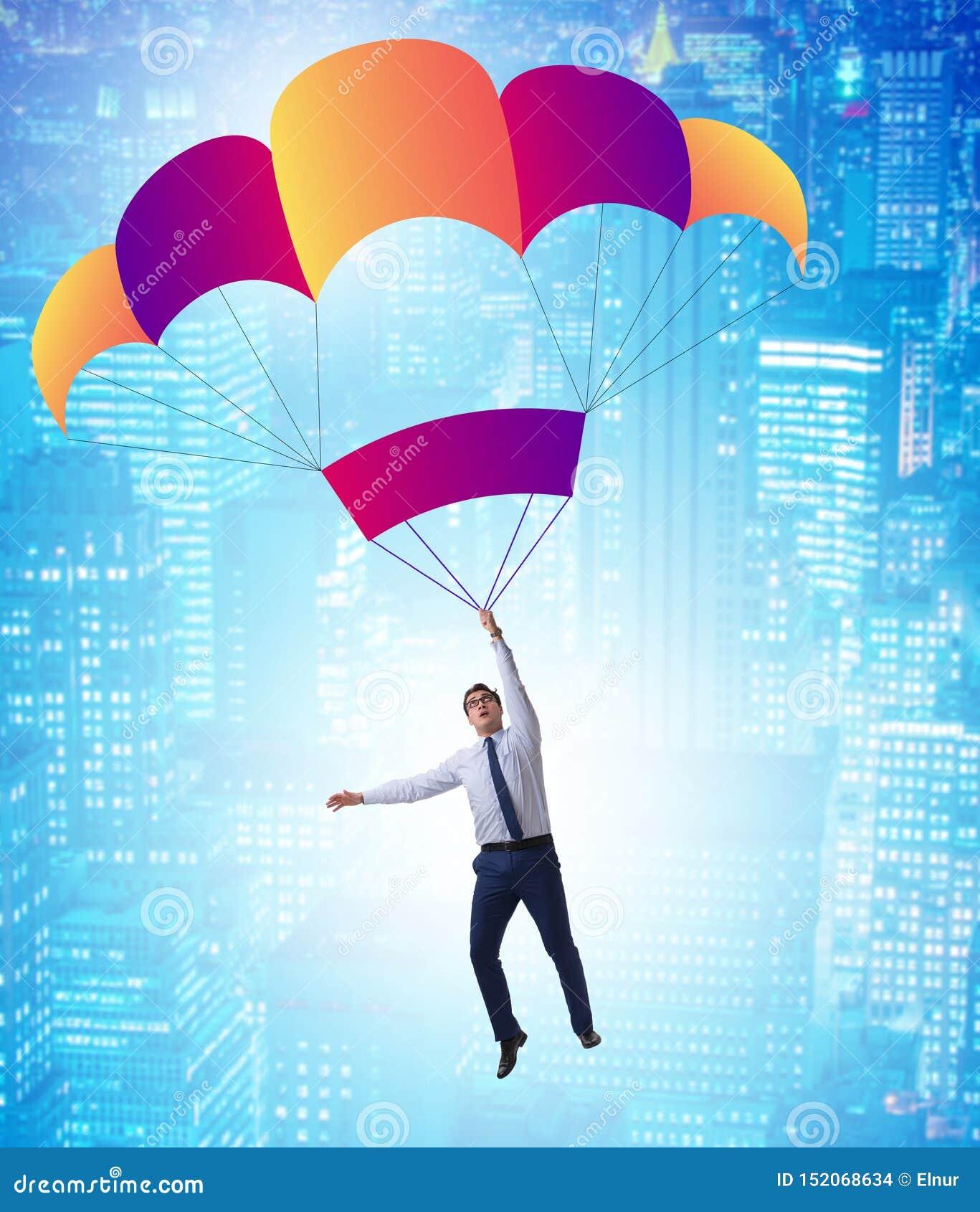 Hombre de negocios joven que cae en el paraca?das en concepto del negocio