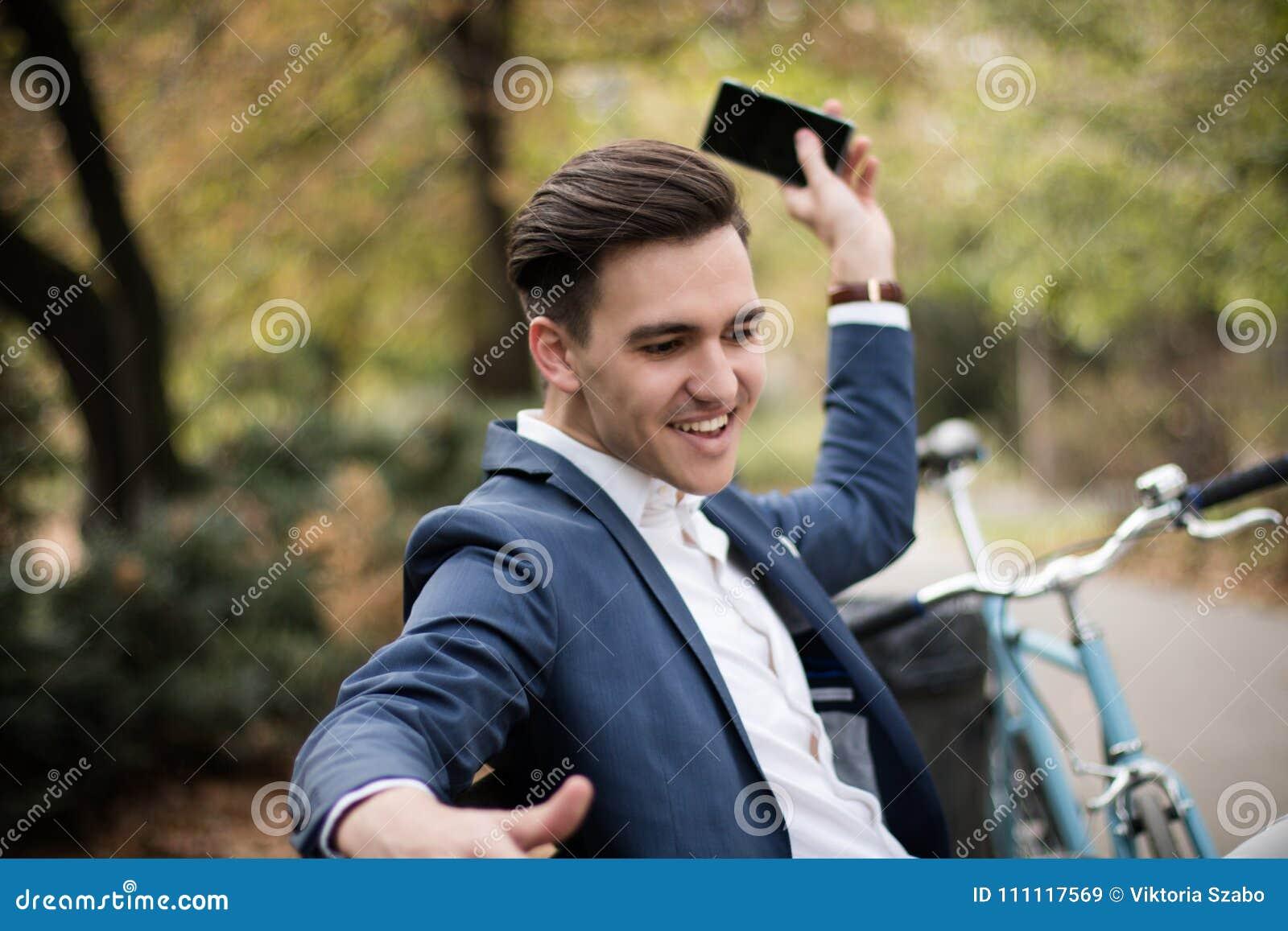 Hombre de negocios joven que lanza lejos su smartphone en el parque