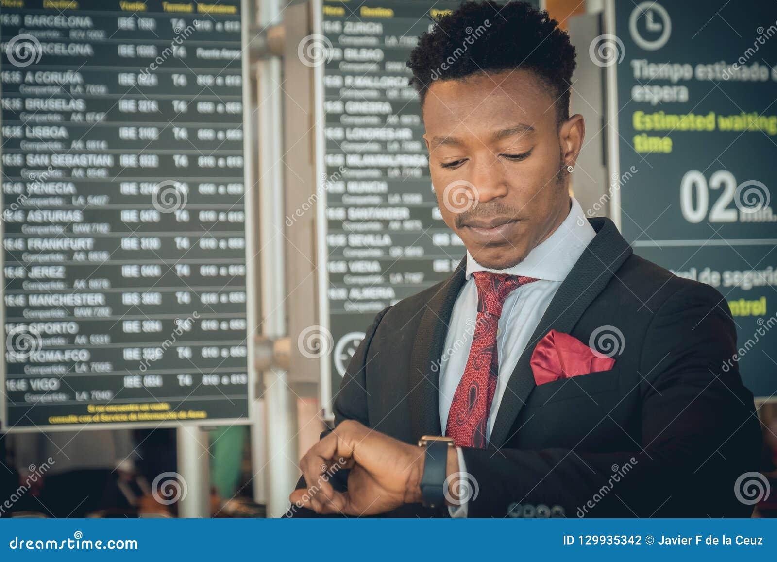 Hombre de negocios joven que mira su reloj elegante en el aeropuerto en f