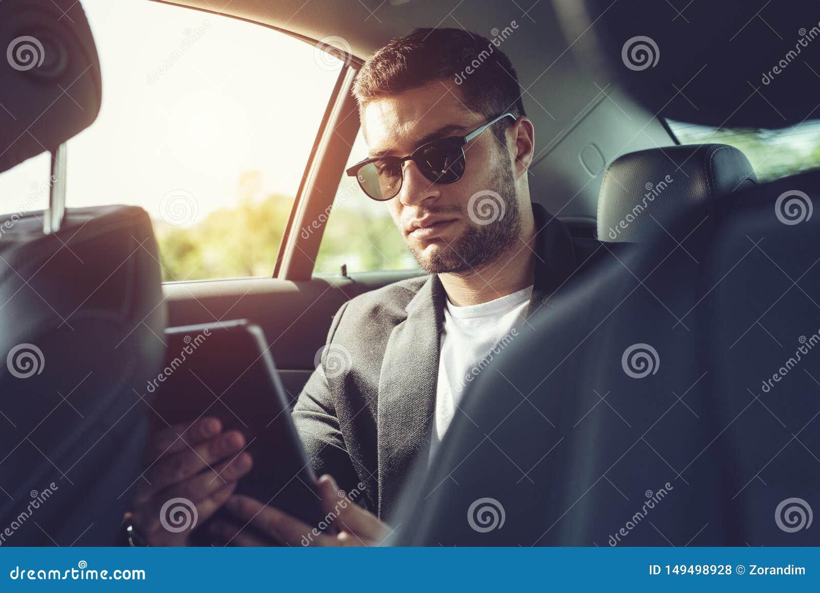 Hombre de negocios joven que se sienta en el asiento trasero del coche y que toca la tableta digital