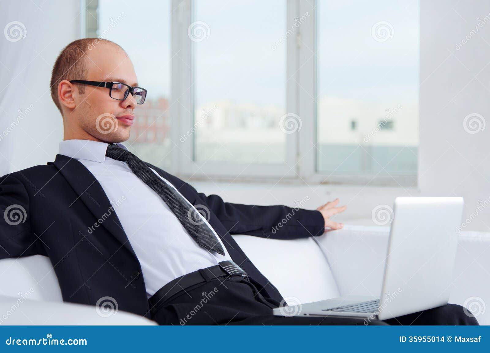 Hombre de negocios joven que se sienta en el sofá con el ordenador portátil