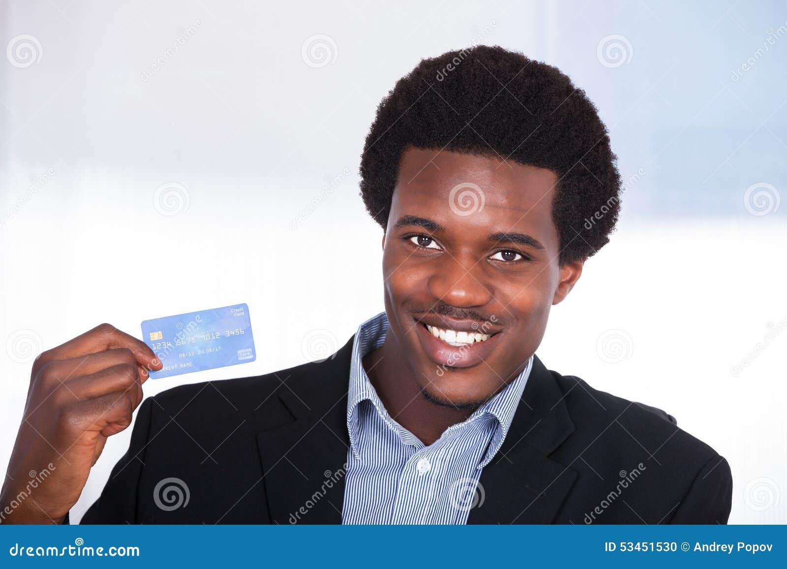 Hombre de negocios joven que sostiene la tarjeta de crédito