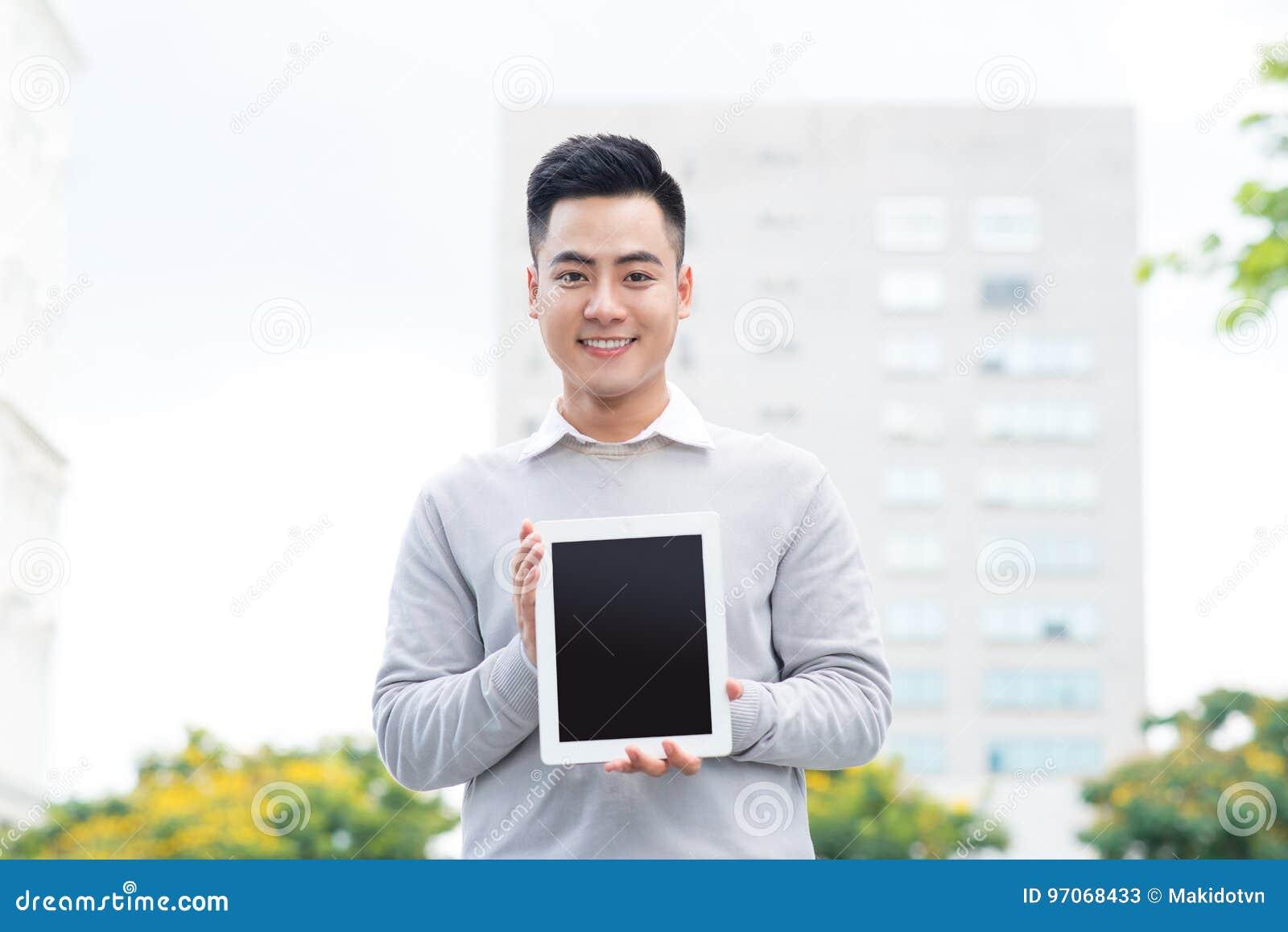 Hombre de negocios joven que sostiene y que muestra la pantalla de la tableta