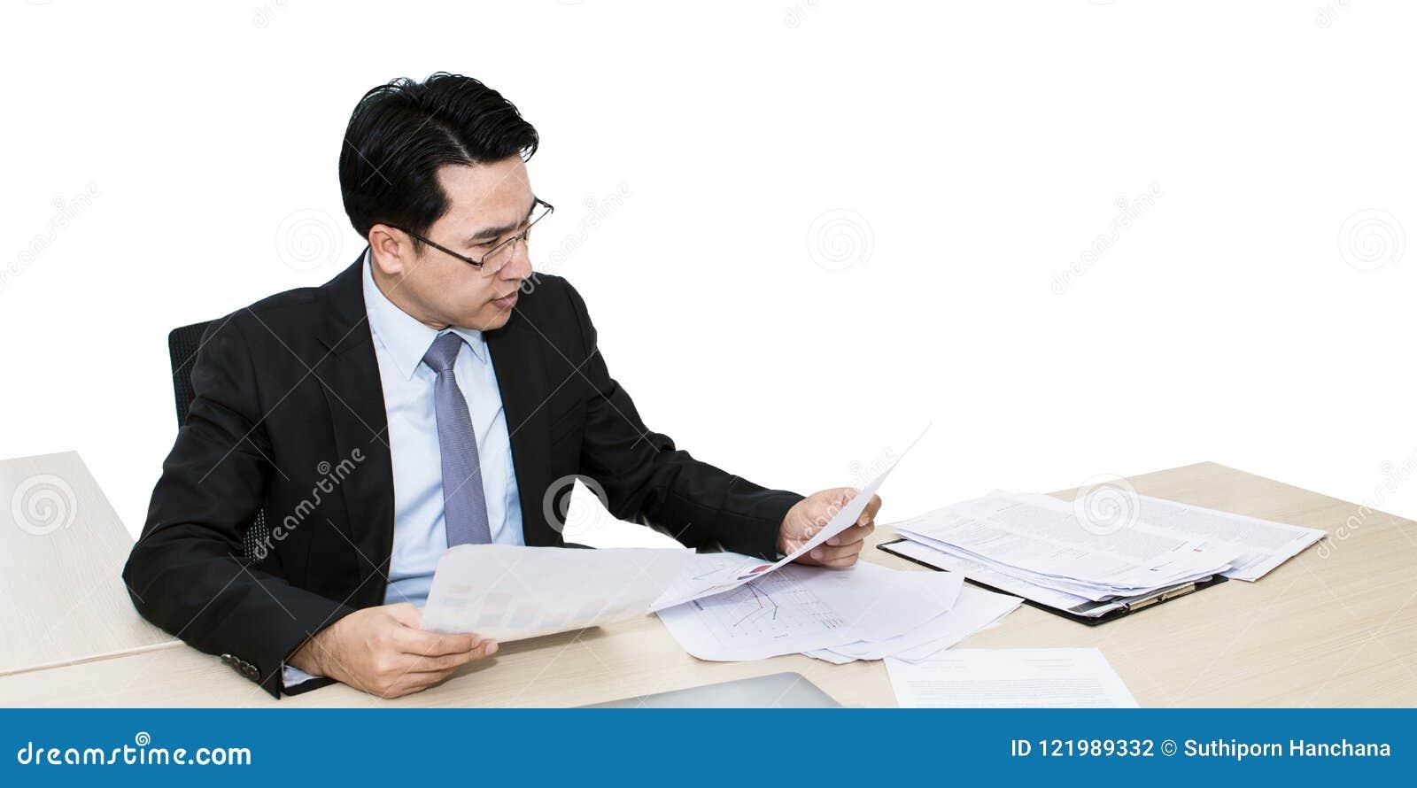 Hombre de negocios joven que trabaja con el ordenador portátil y los materiales de oficina