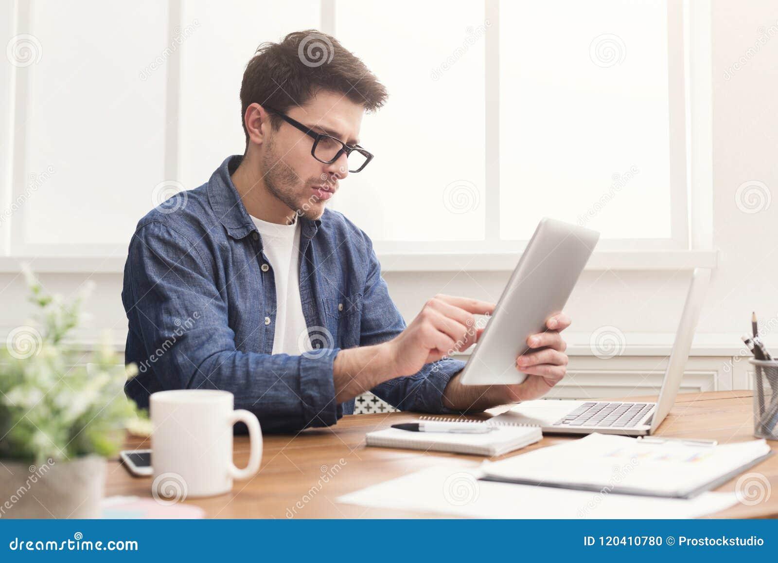 Hombre de negocios joven que trabaja con la tableta digital en oficina
