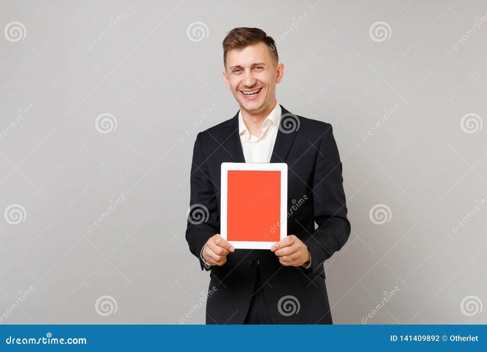 Hombre de negocios joven de risa en el traje negro clásico, ordenador de la PC de la tableta de la tenencia de la camisa con la p