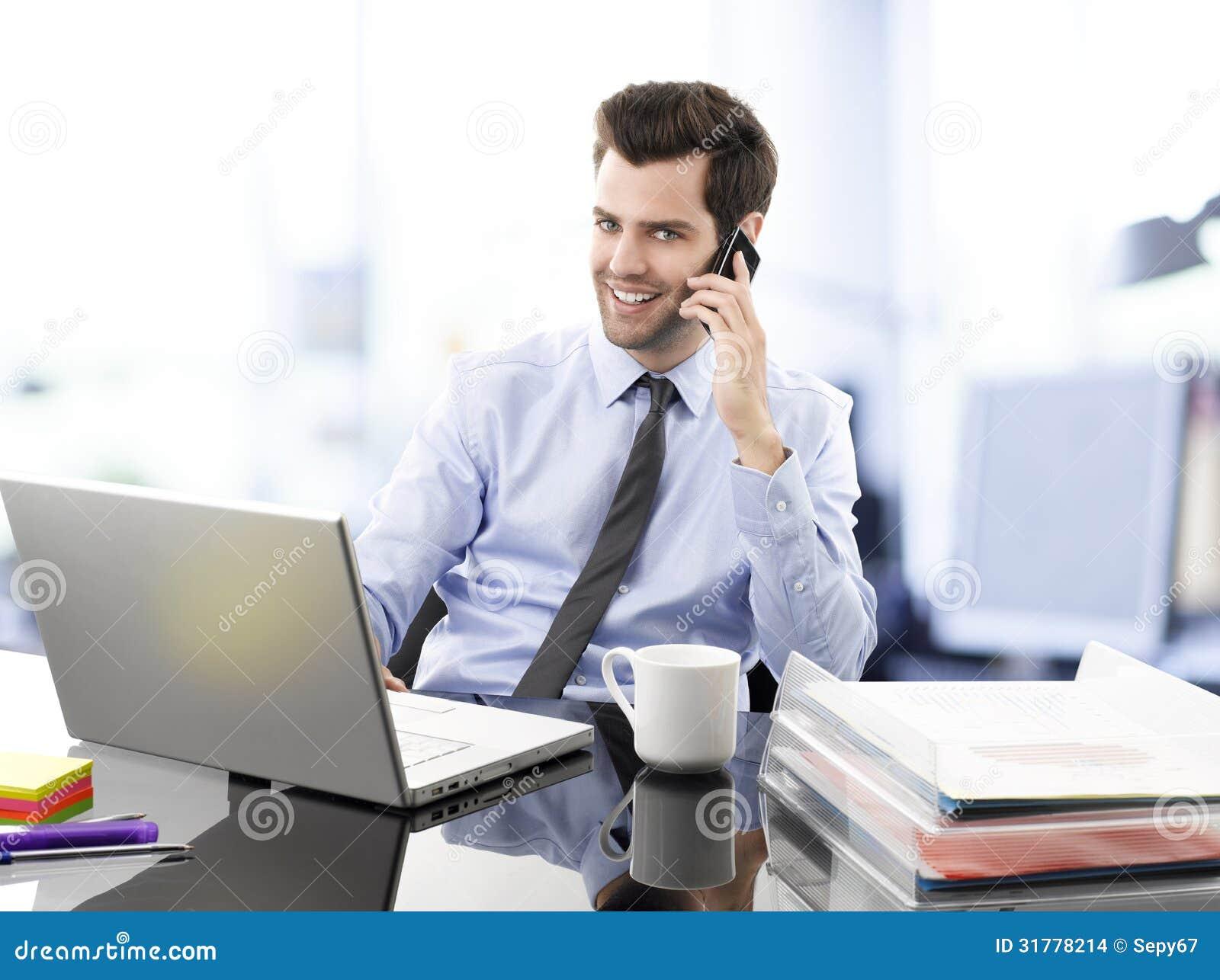 Hombre de negocios joven sonriente que habla en el for Telefono oficina