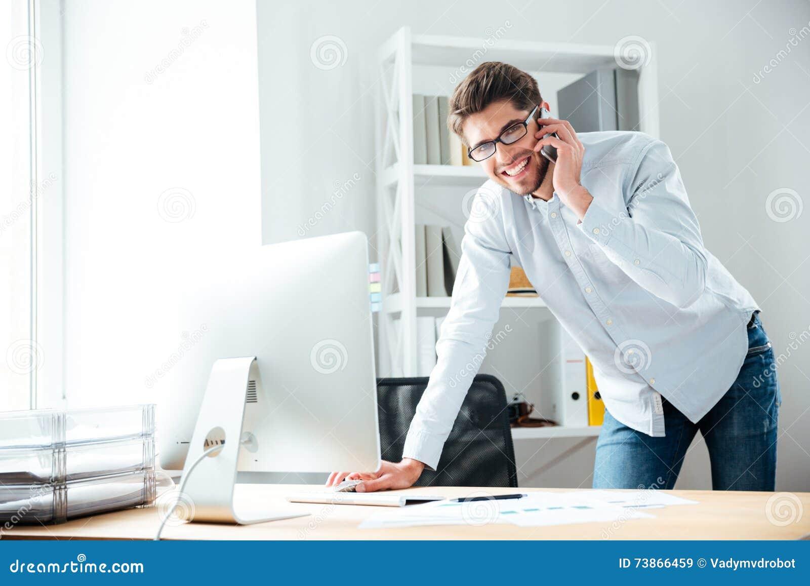 Hombre de negocios joven sonriente usando el ordenador y el hablar en el teléfono móvil