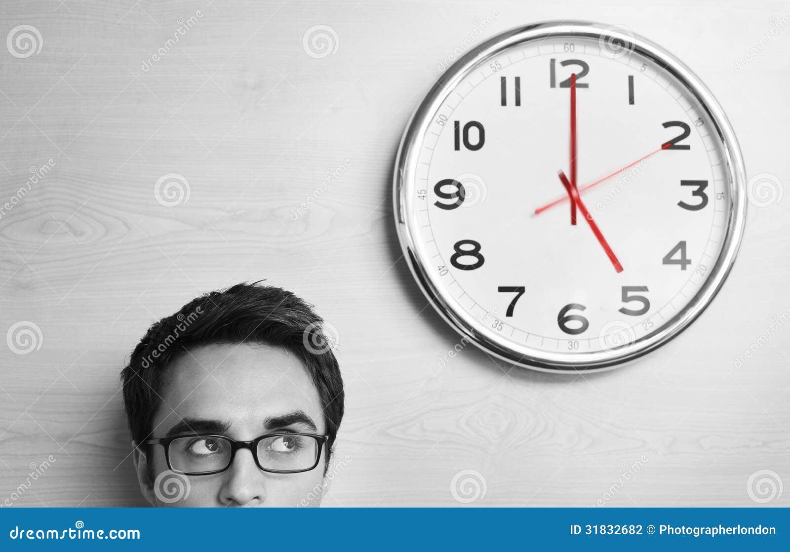 Hombre de negocios Looking At Clock en la pared de madera
