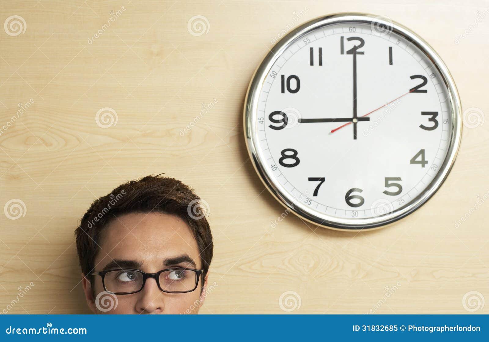 Hombre de negocios Looking At Clock en la pared de madera en oficina