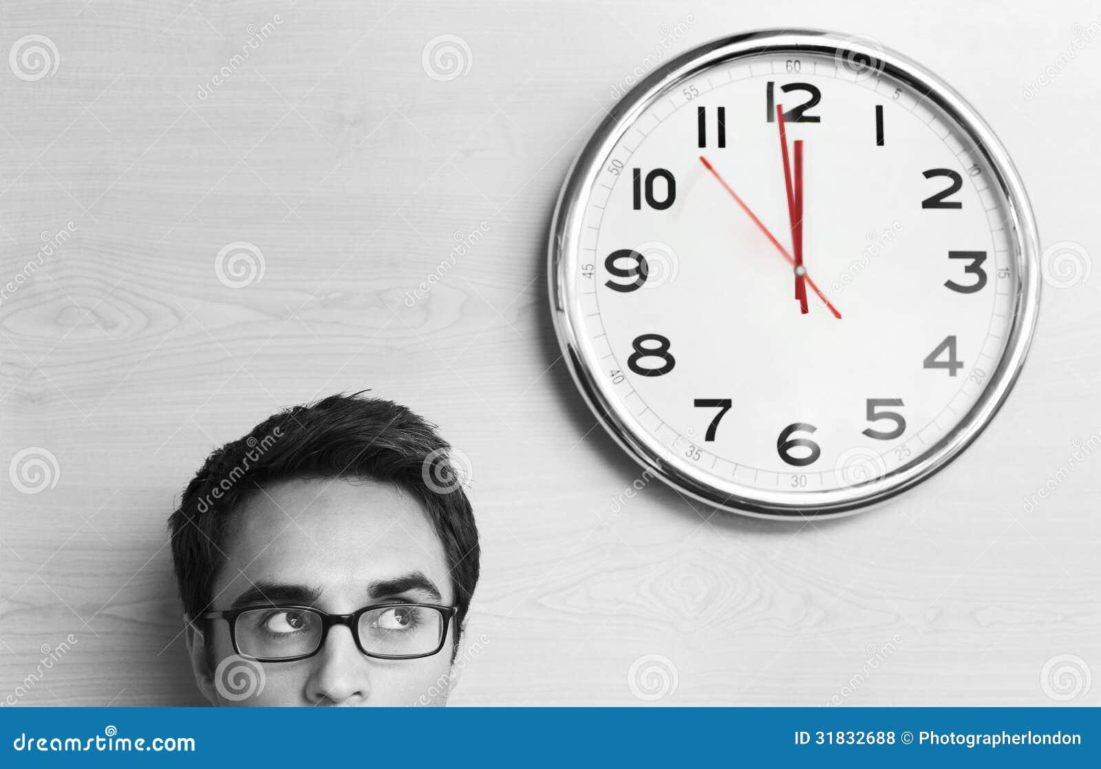 Hombre de negocios Looking At Clock en la pared en oficina