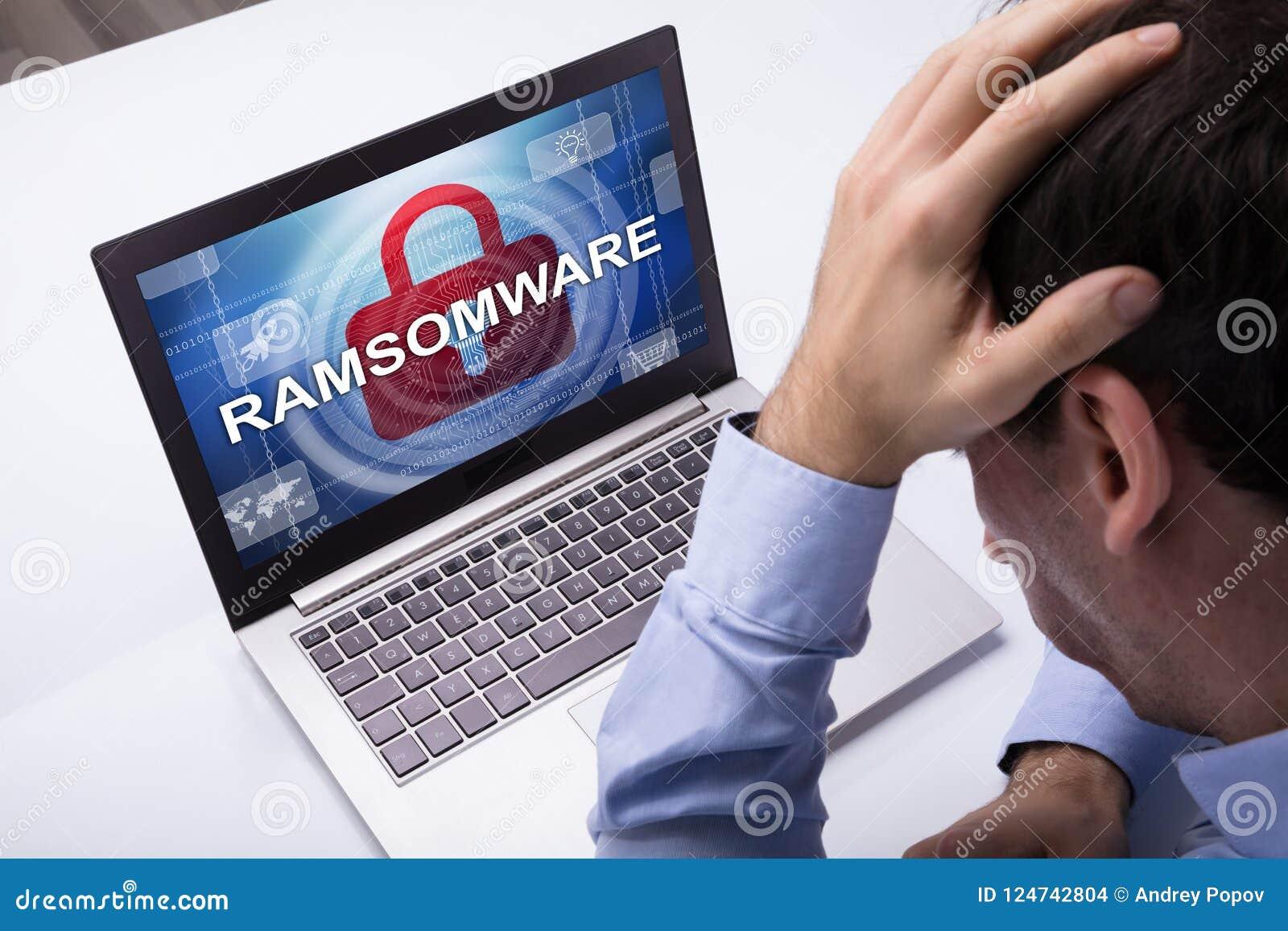 Hombre de negocios Looking At Laptop con la palabra de Ramsomware en la pantalla
