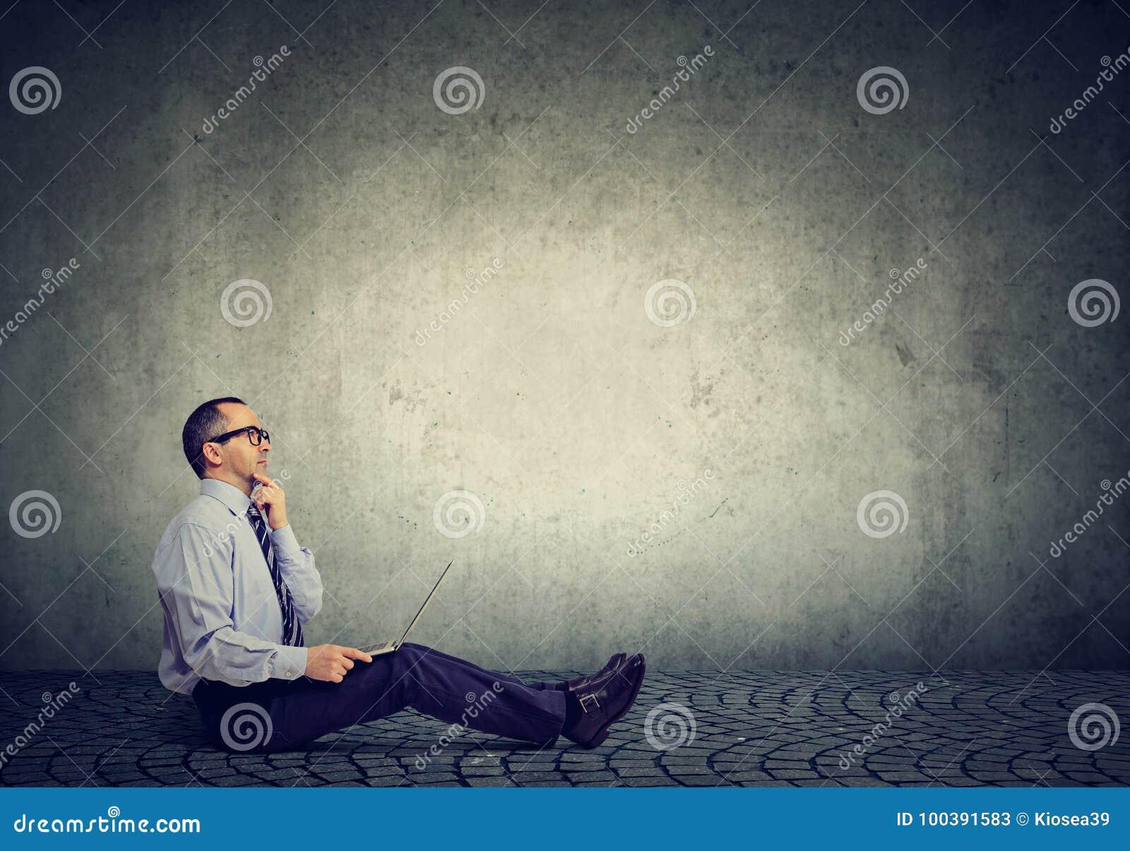 Hombre de negocios maduros con el ordenador portátil que se sienta en un pensamiento del piso