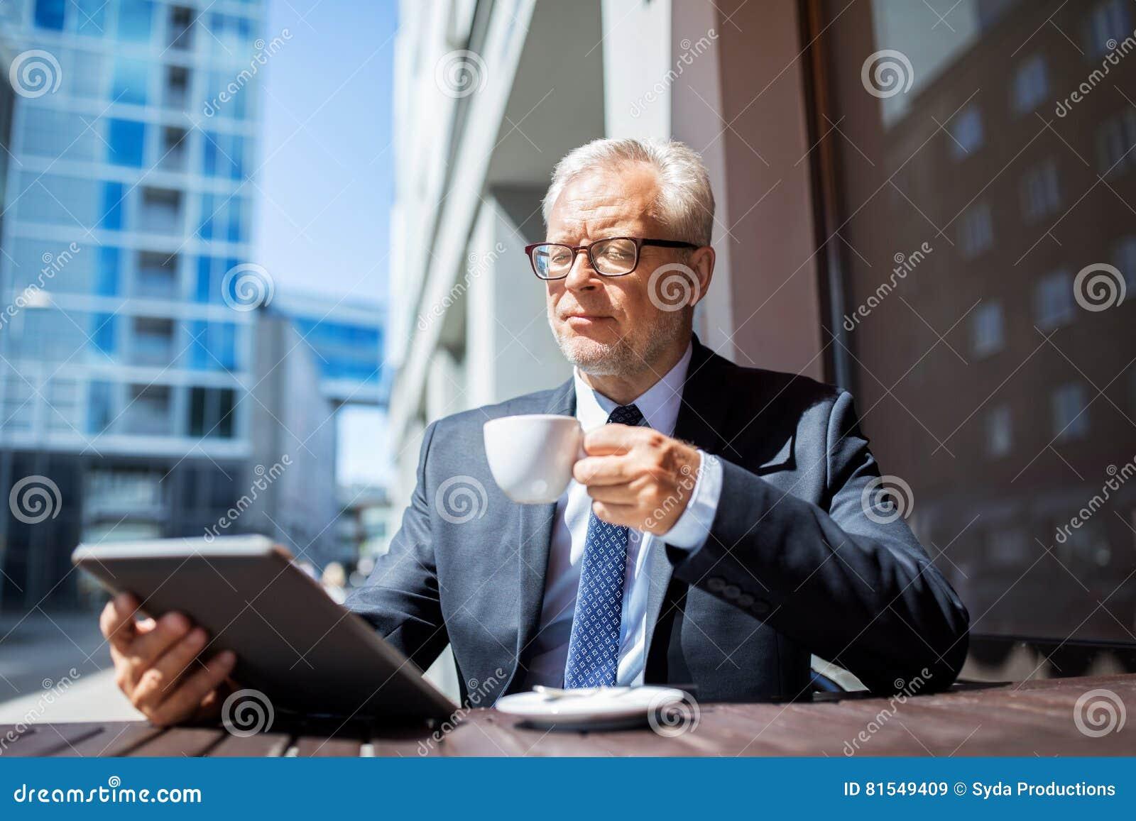 Hombre de negocios mayor con café de consumición de la PC de la tableta