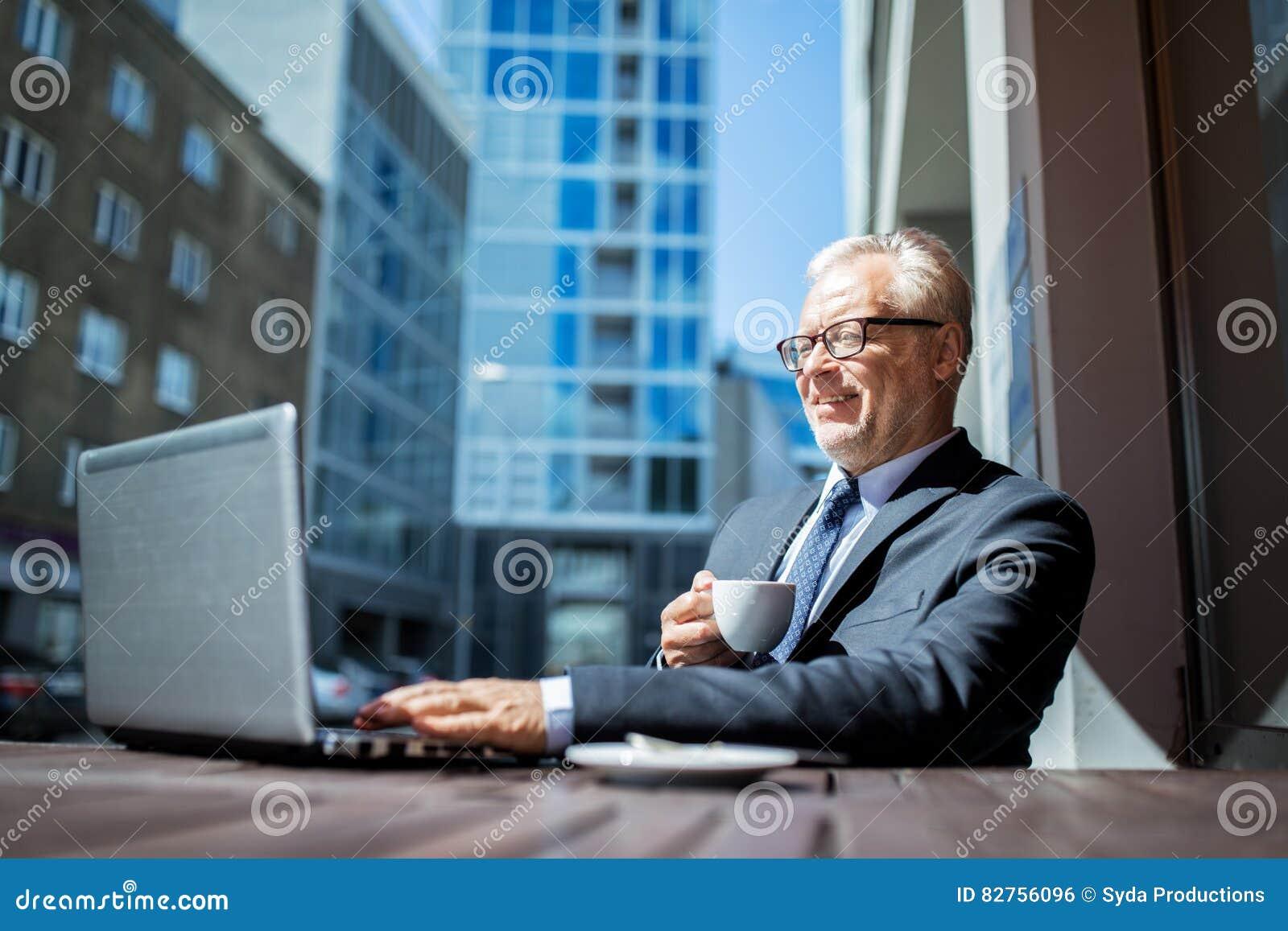 Hombre de negocios mayor con café de consumición del ordenador portátil