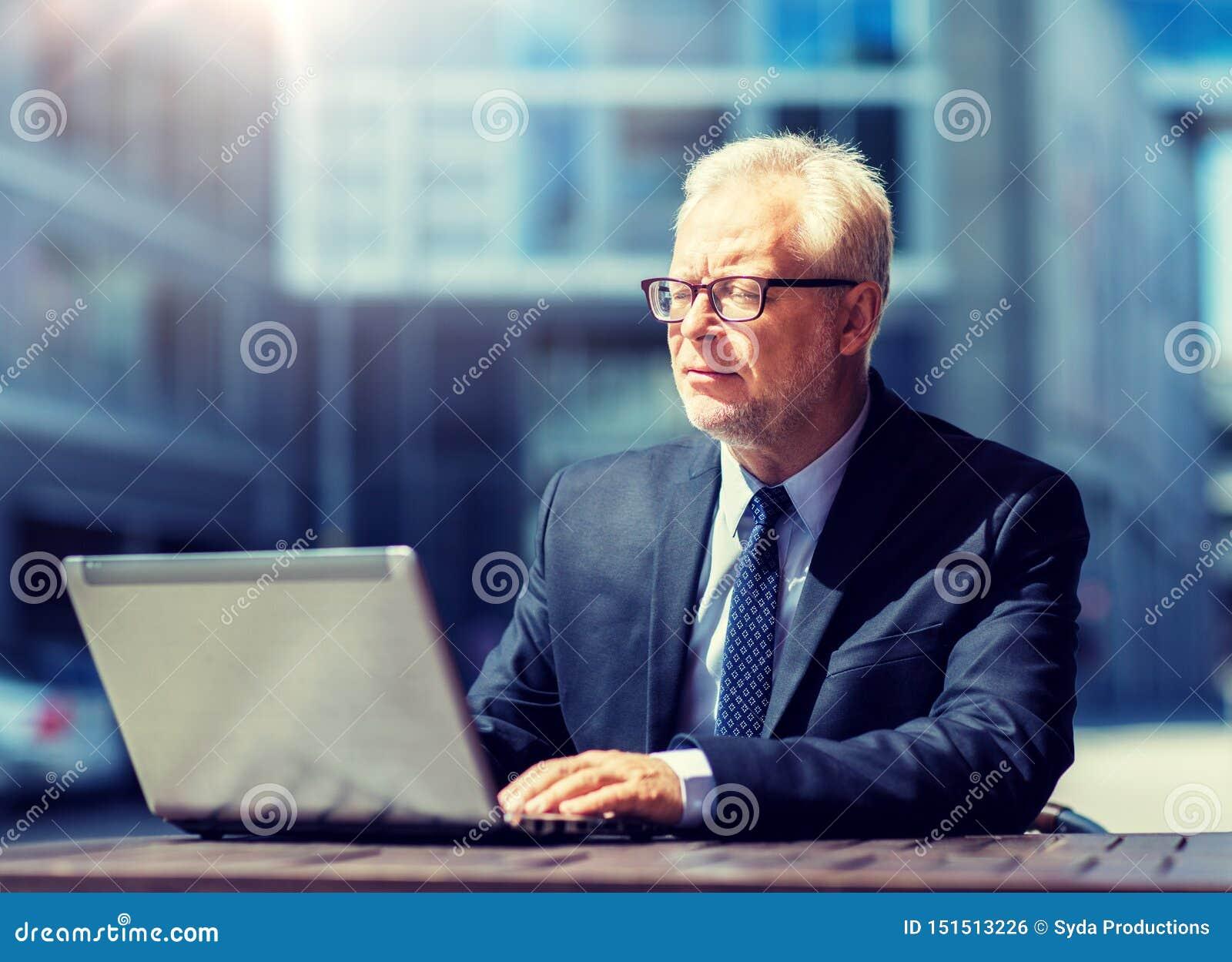 Hombre de negocios mayor con el ordenador port?til en el caf? de la calle de la ciudad