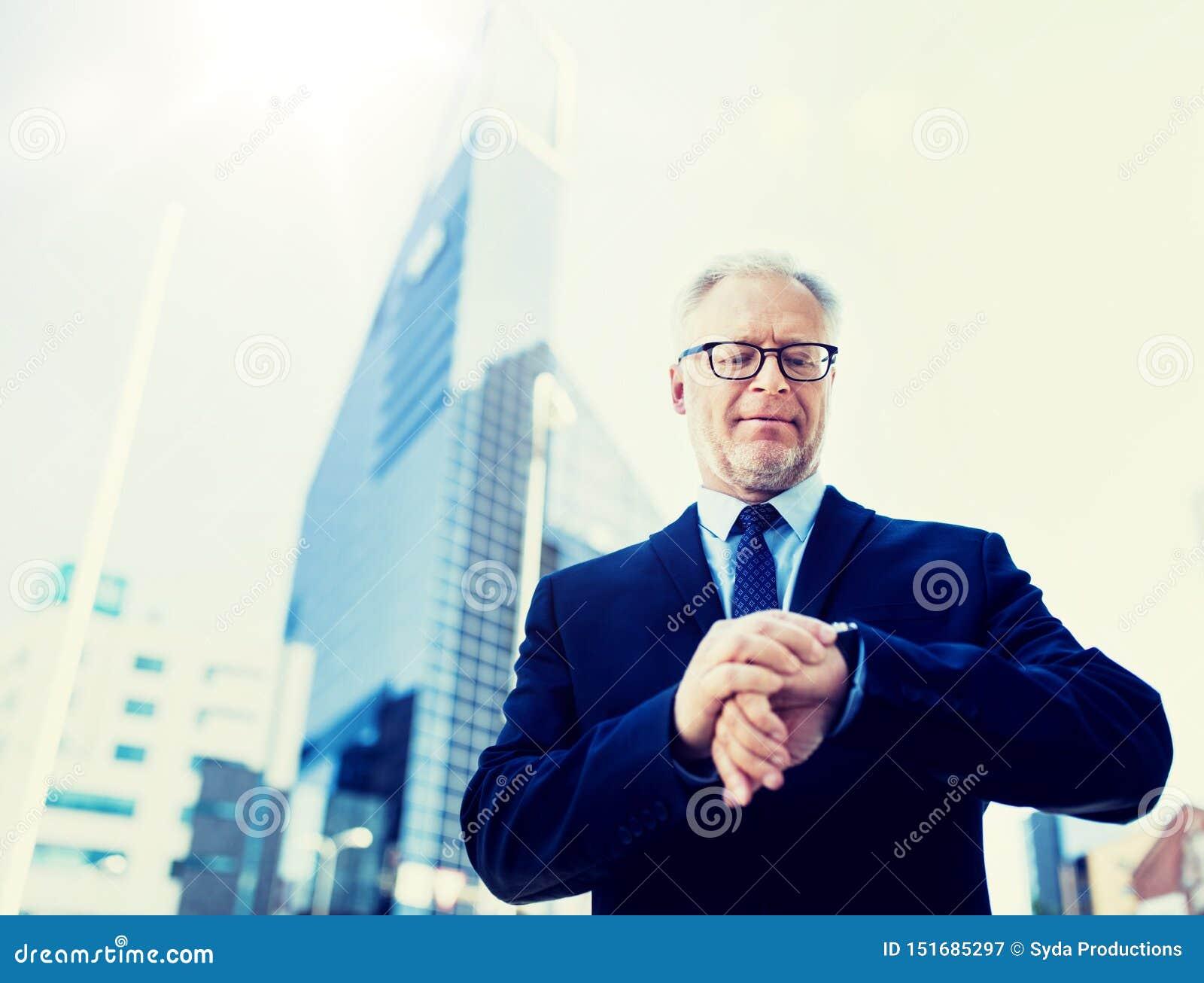 Hombre de negocios mayor que comprueba tiempo en su reloj