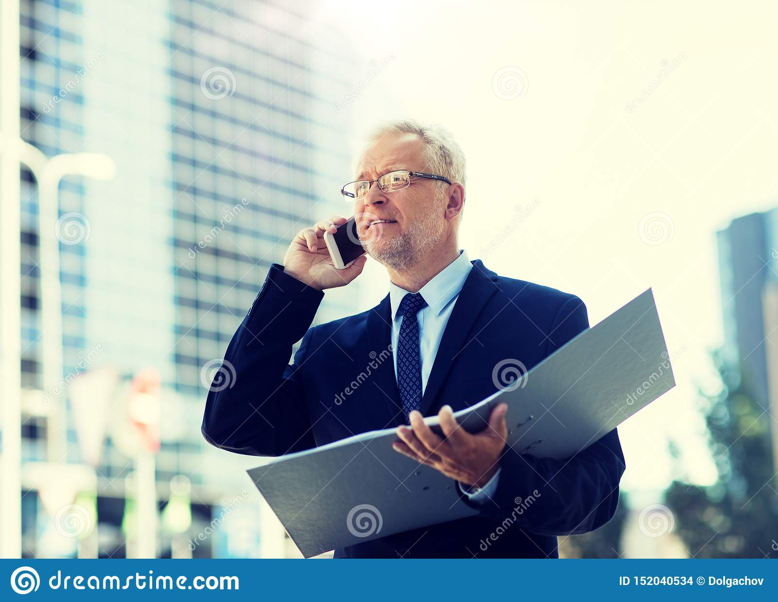 Hombre de negocios mayor que invita a smartphone en ciudad