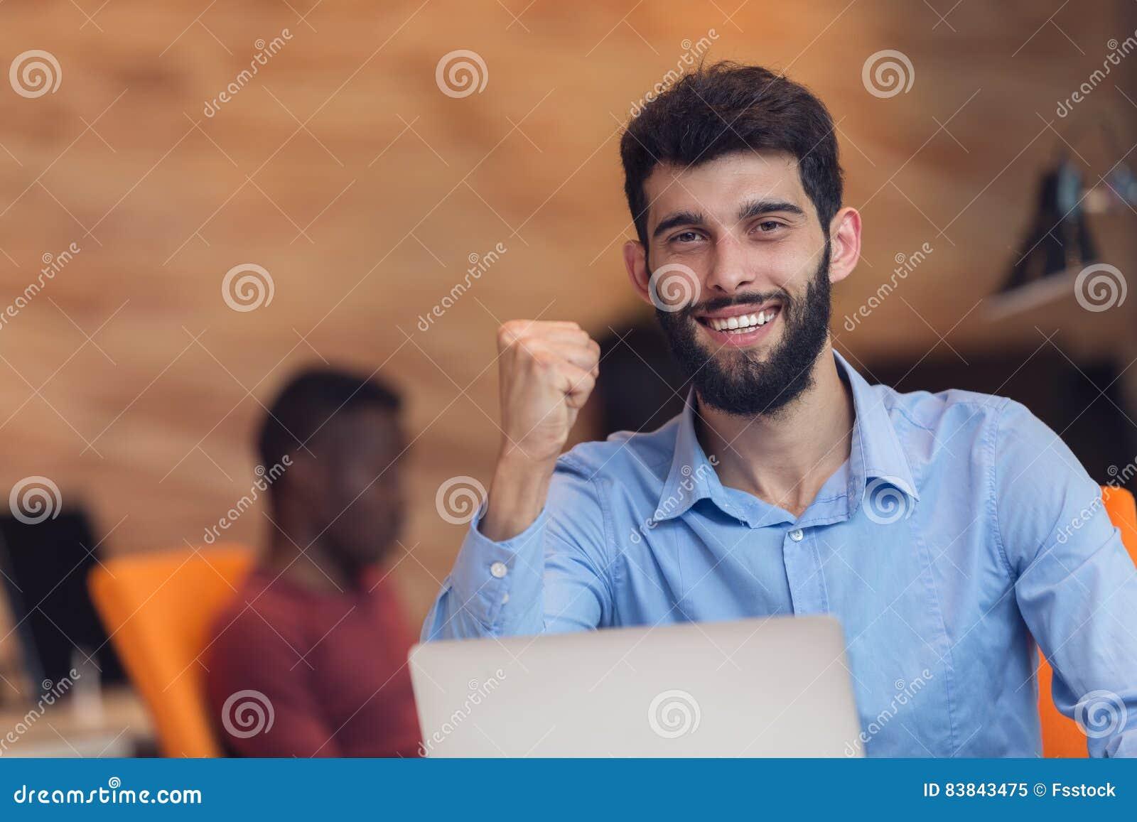 Hombre de negocios moderno caucásico barbudo joven que se sienta en una oficina de lanzamiento